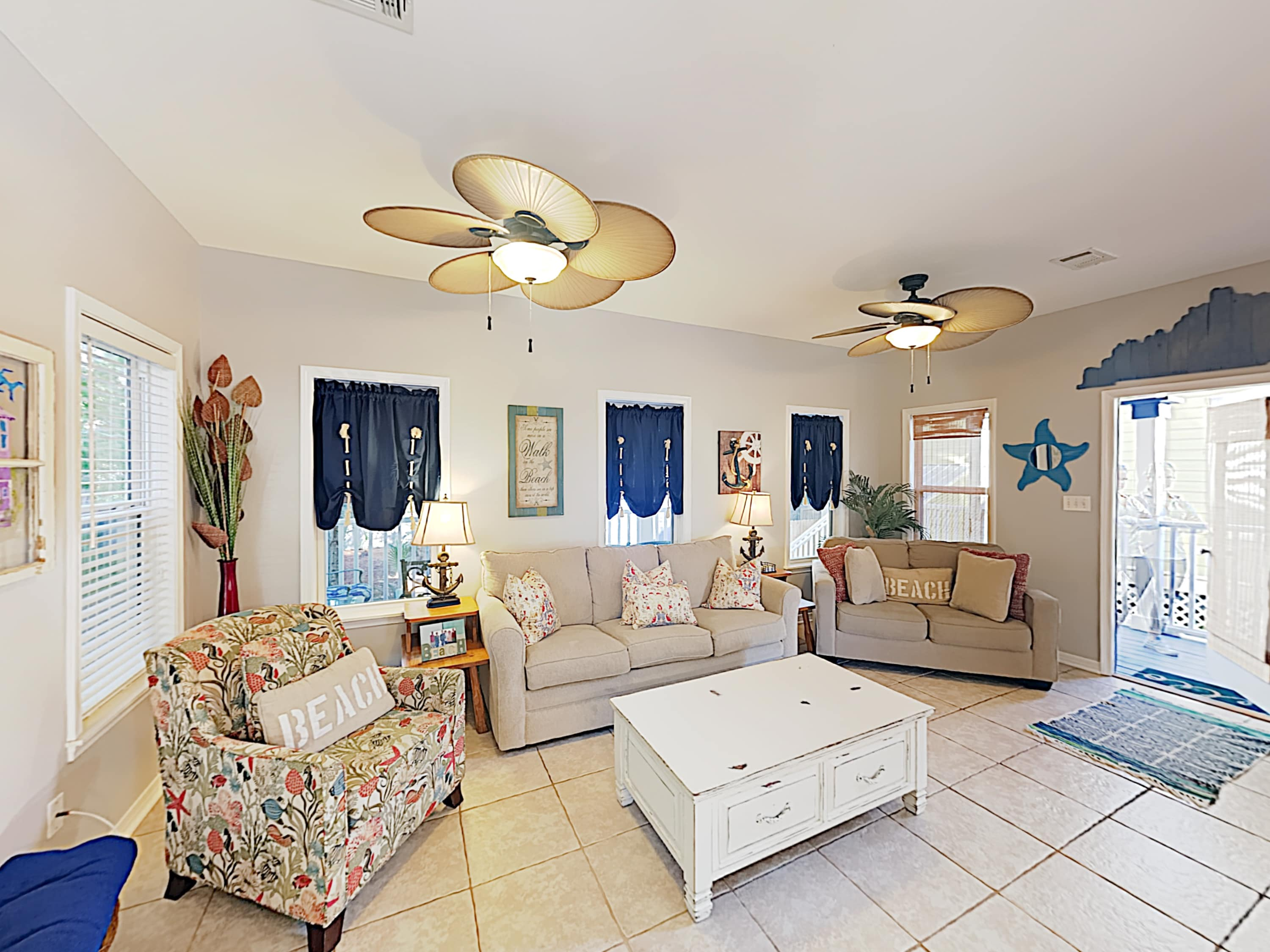 The cozy living area has seaside decor and seating for 6 on a sofa, love seat, and armchair.