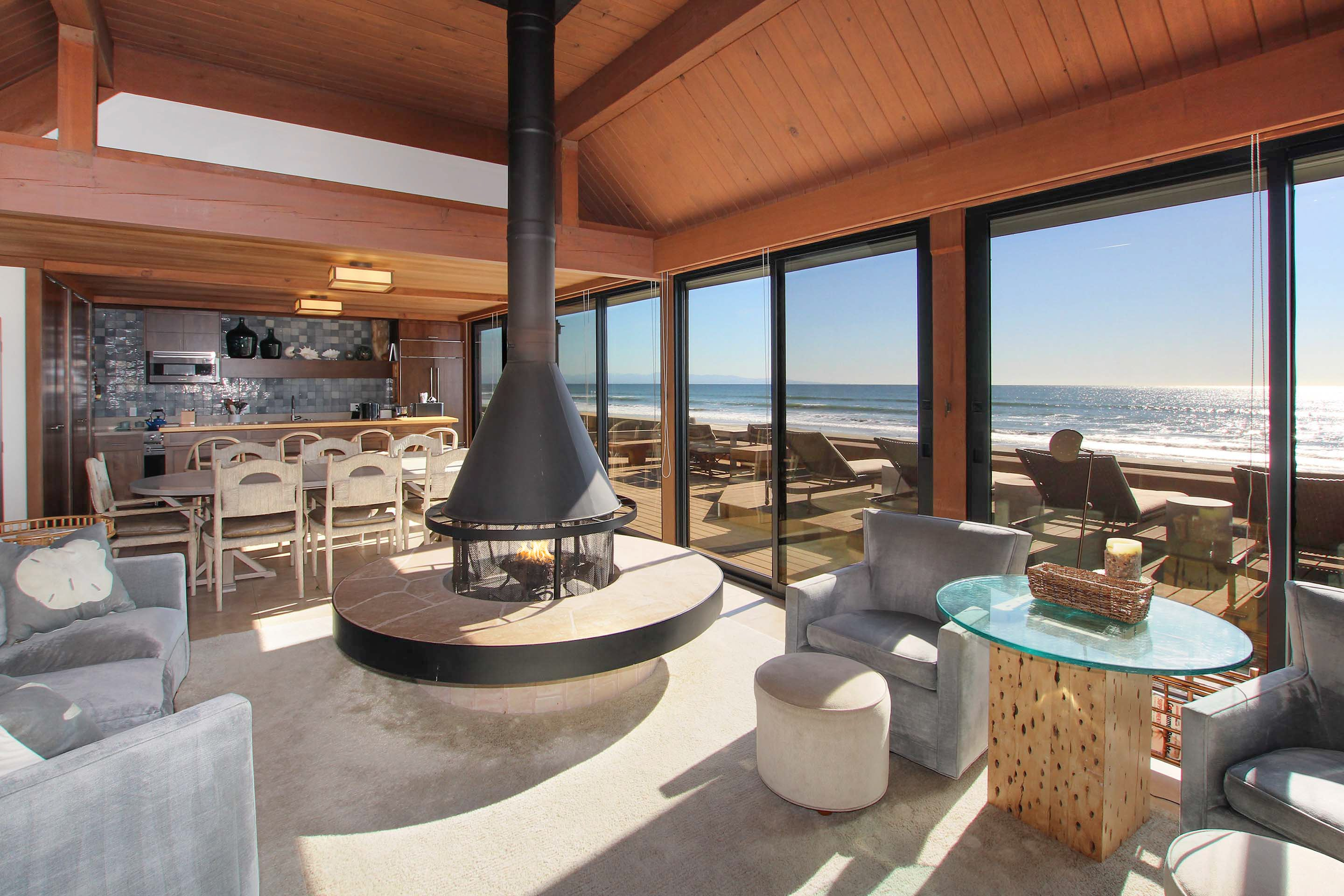 Unwind with a a gas fireplace and sweeping ocean views in the open living, dining and kitchen area.
