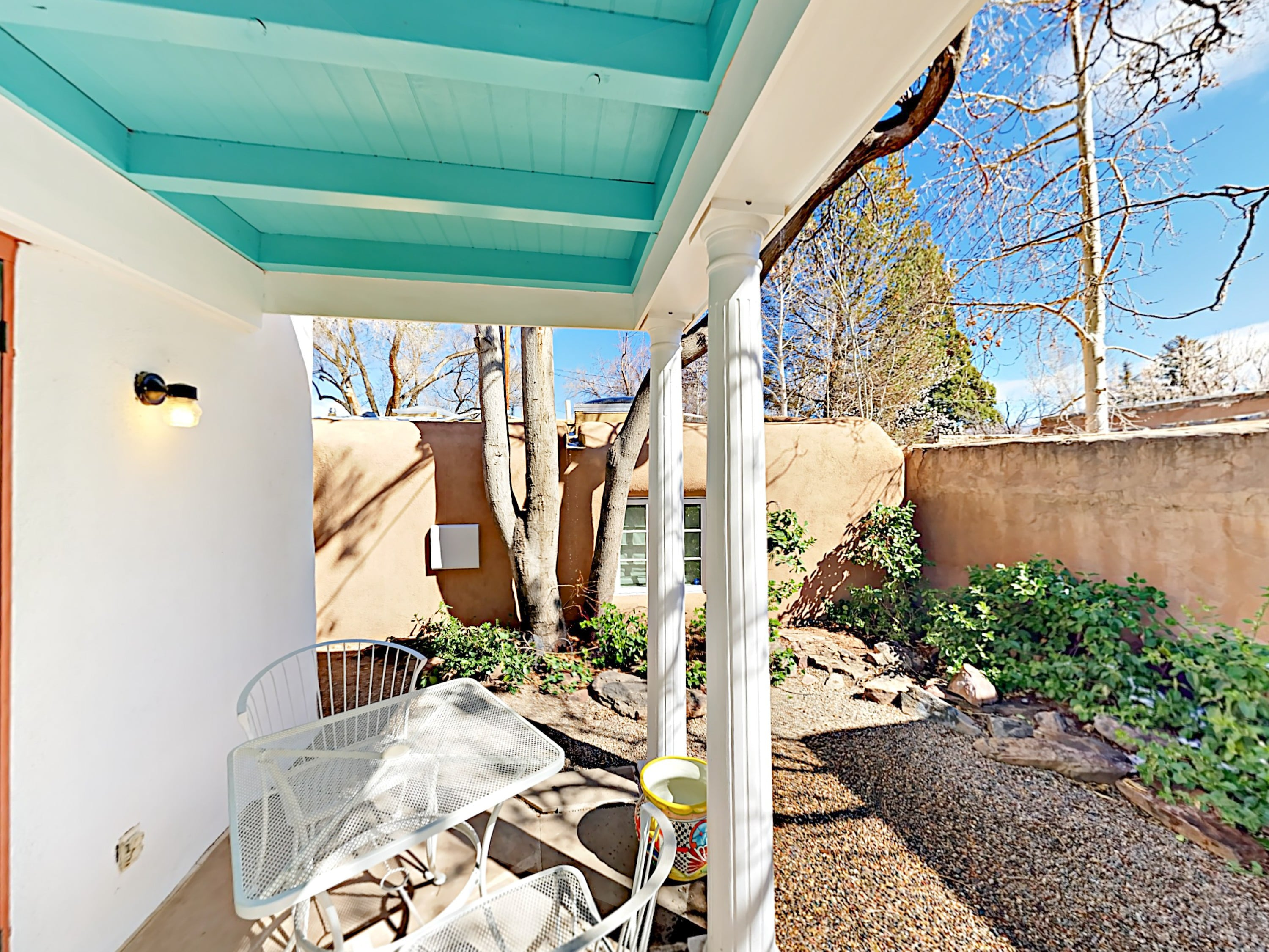 The private garden patio features a covered portal with a bistro table, 2 chairs, and a grill.
