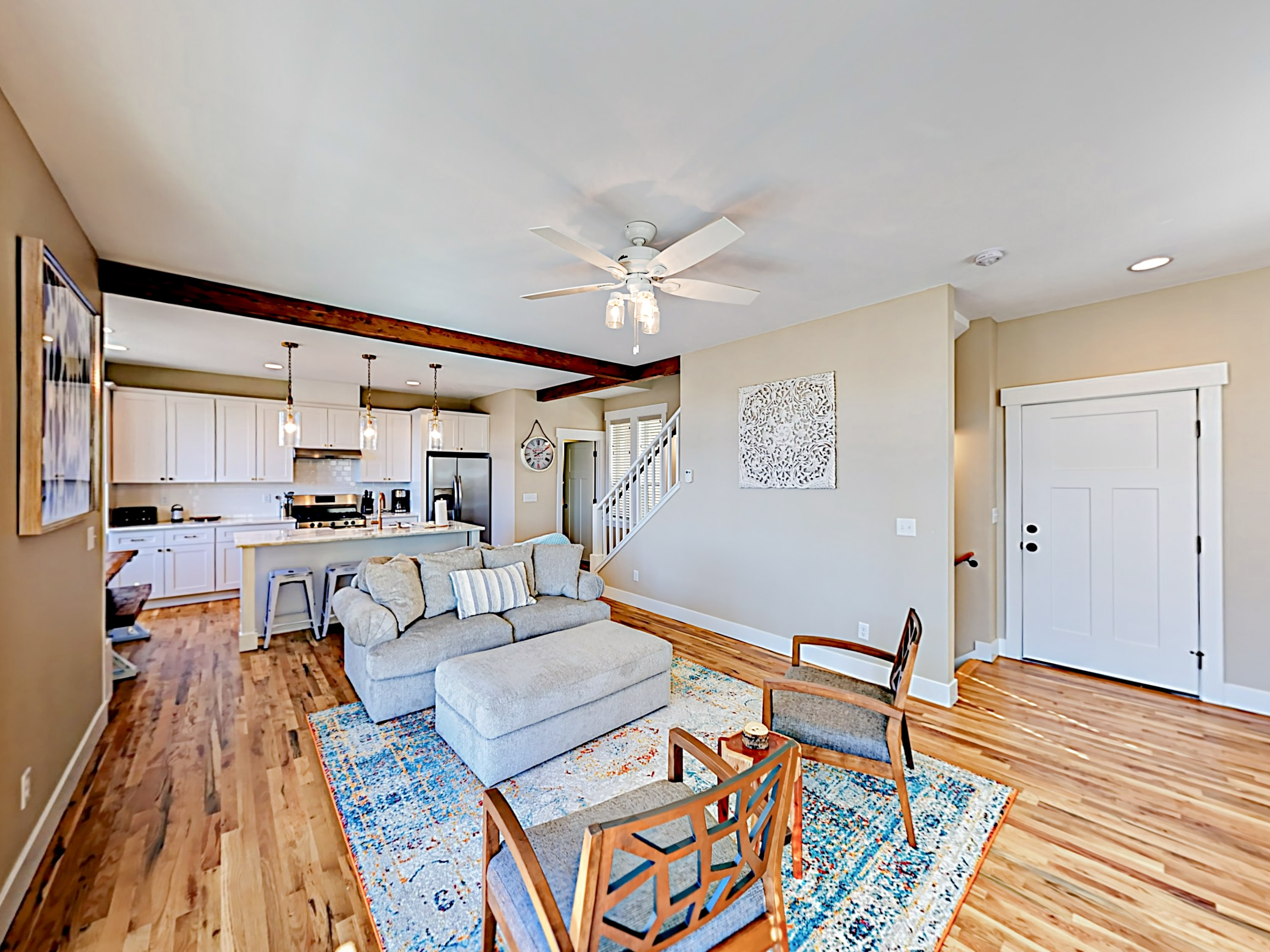 Wood flooring and bright decor highlight the open floor plan in the living area.