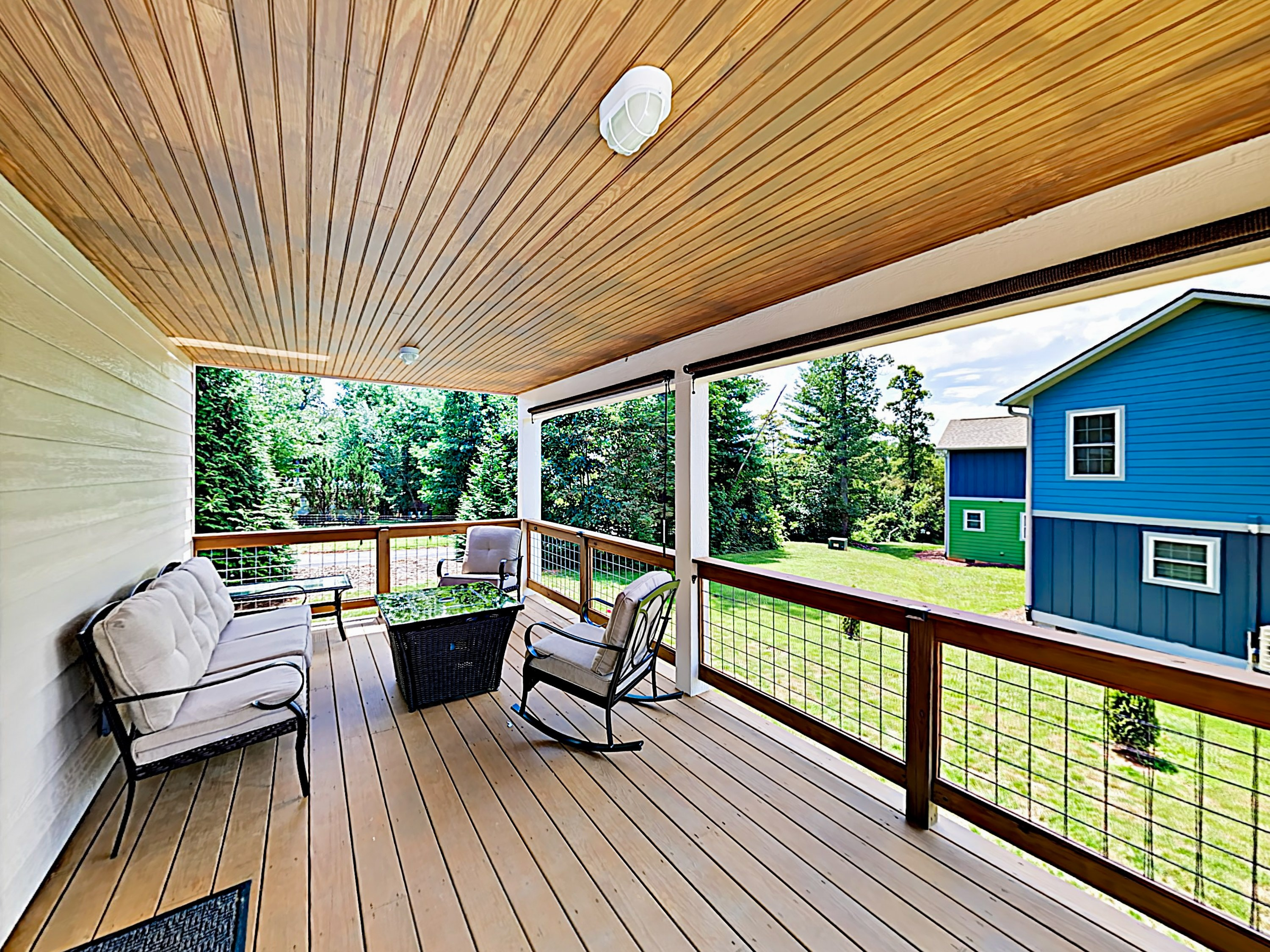 The covered deck is equipped with a cushioned seating area and gas firepit.