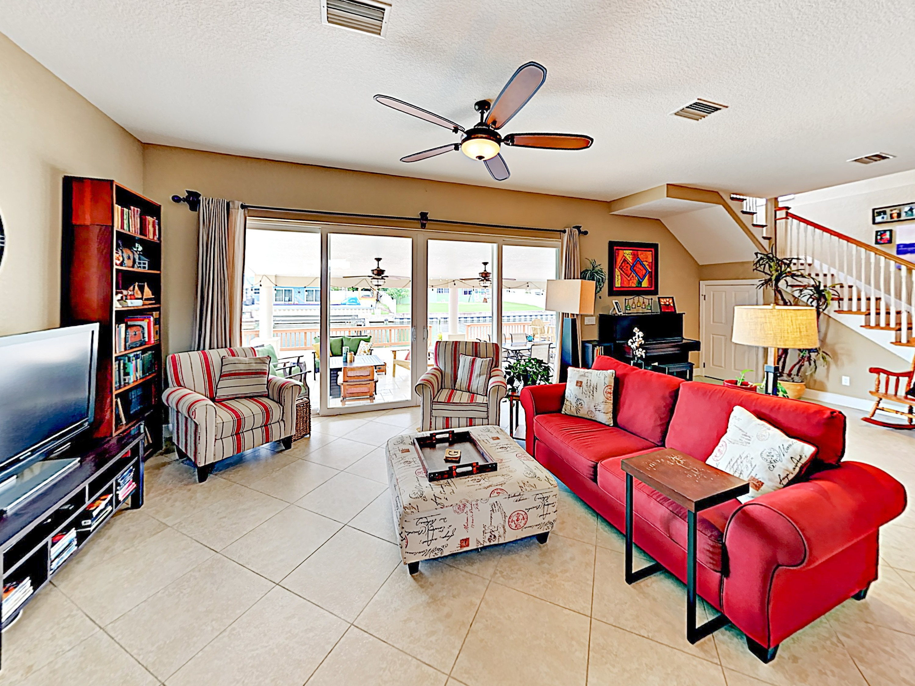 Gather together in the sunny living room, furnished with a bold red love seat and 2 comfy armchairs.