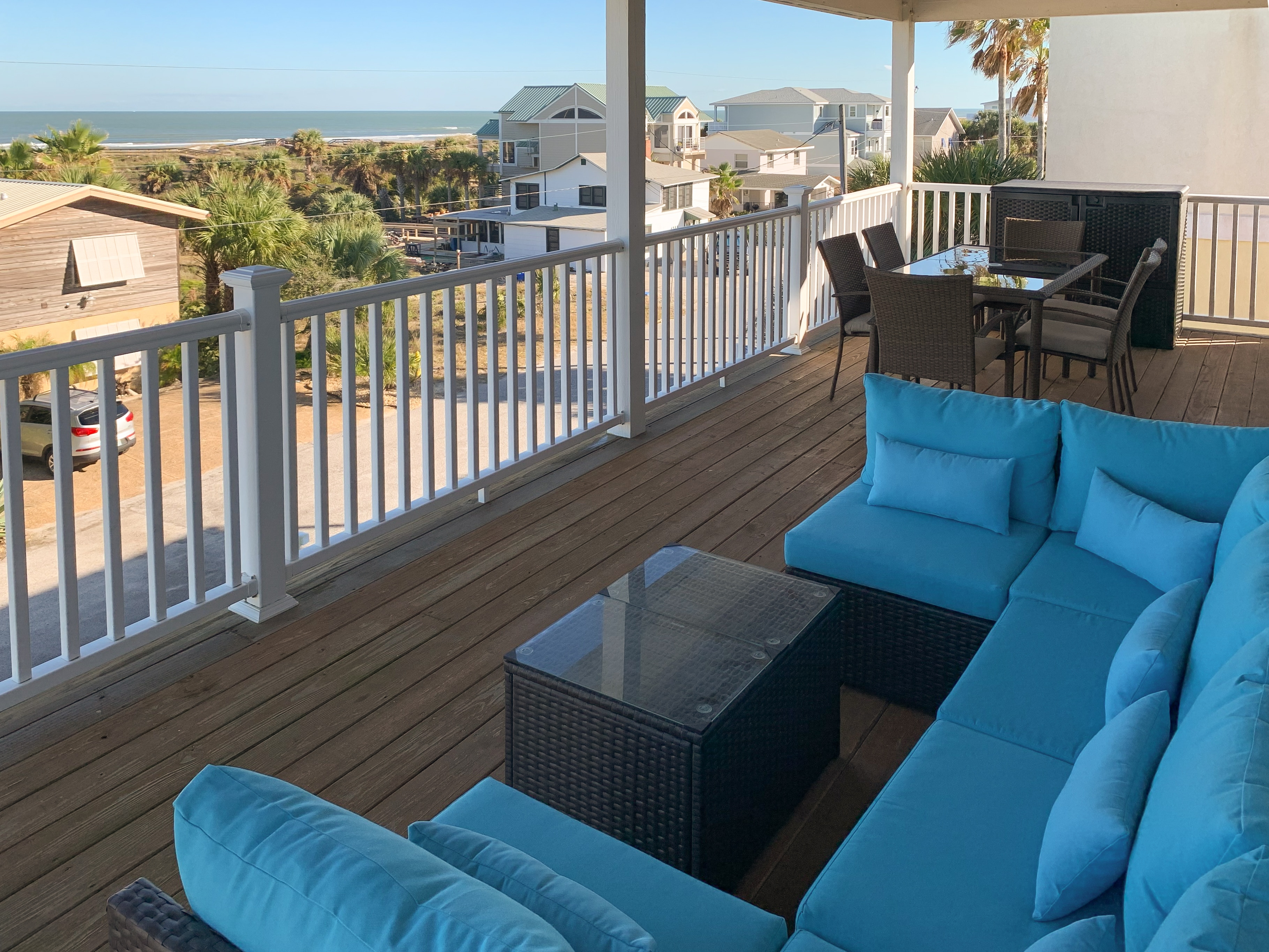 Sweeping ocean views await on the covered balcony, where a comfy sectional offers plenty of seating.