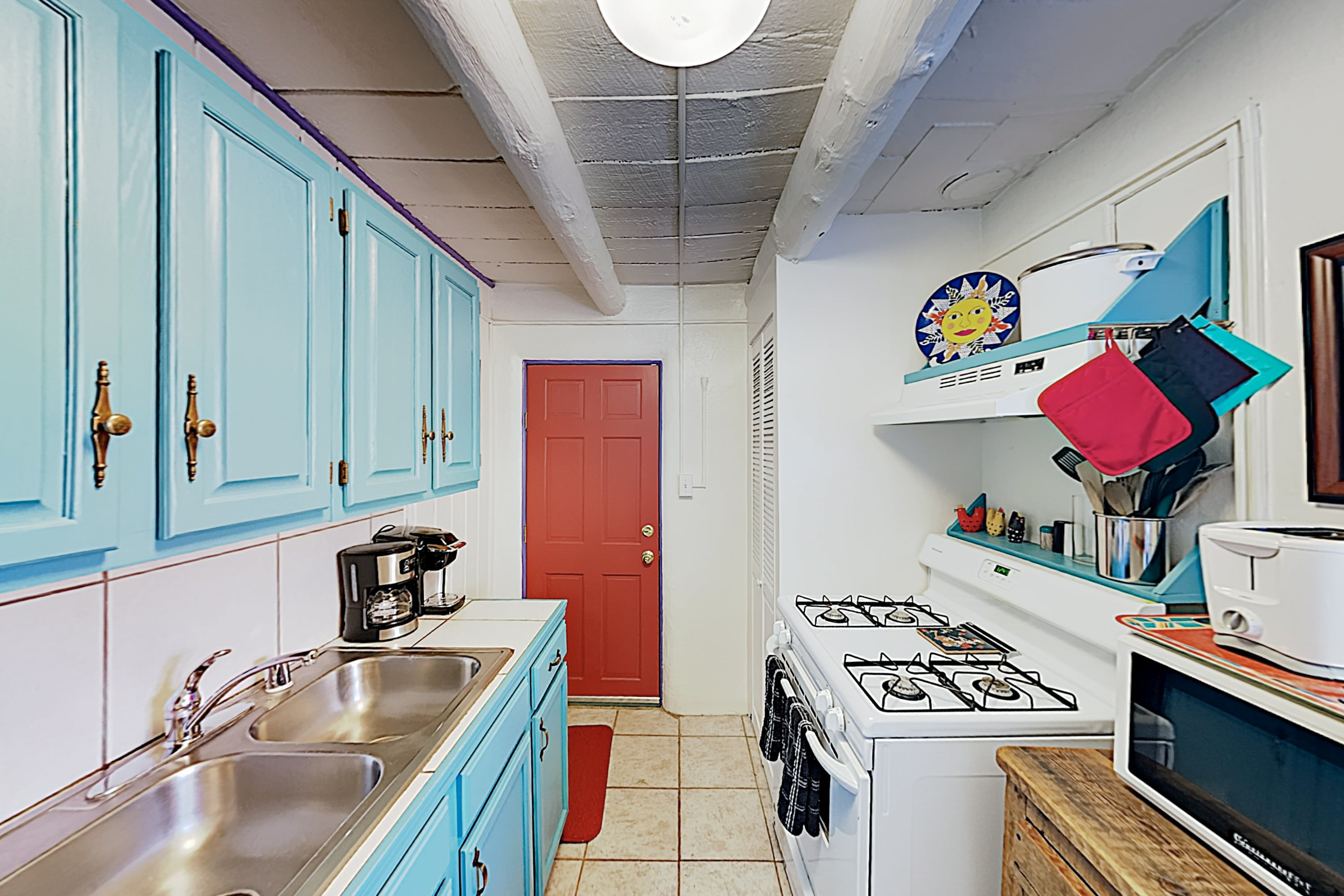 Channel your inner chef in a well-equipped kitchen detailed with colorful cabinetry.