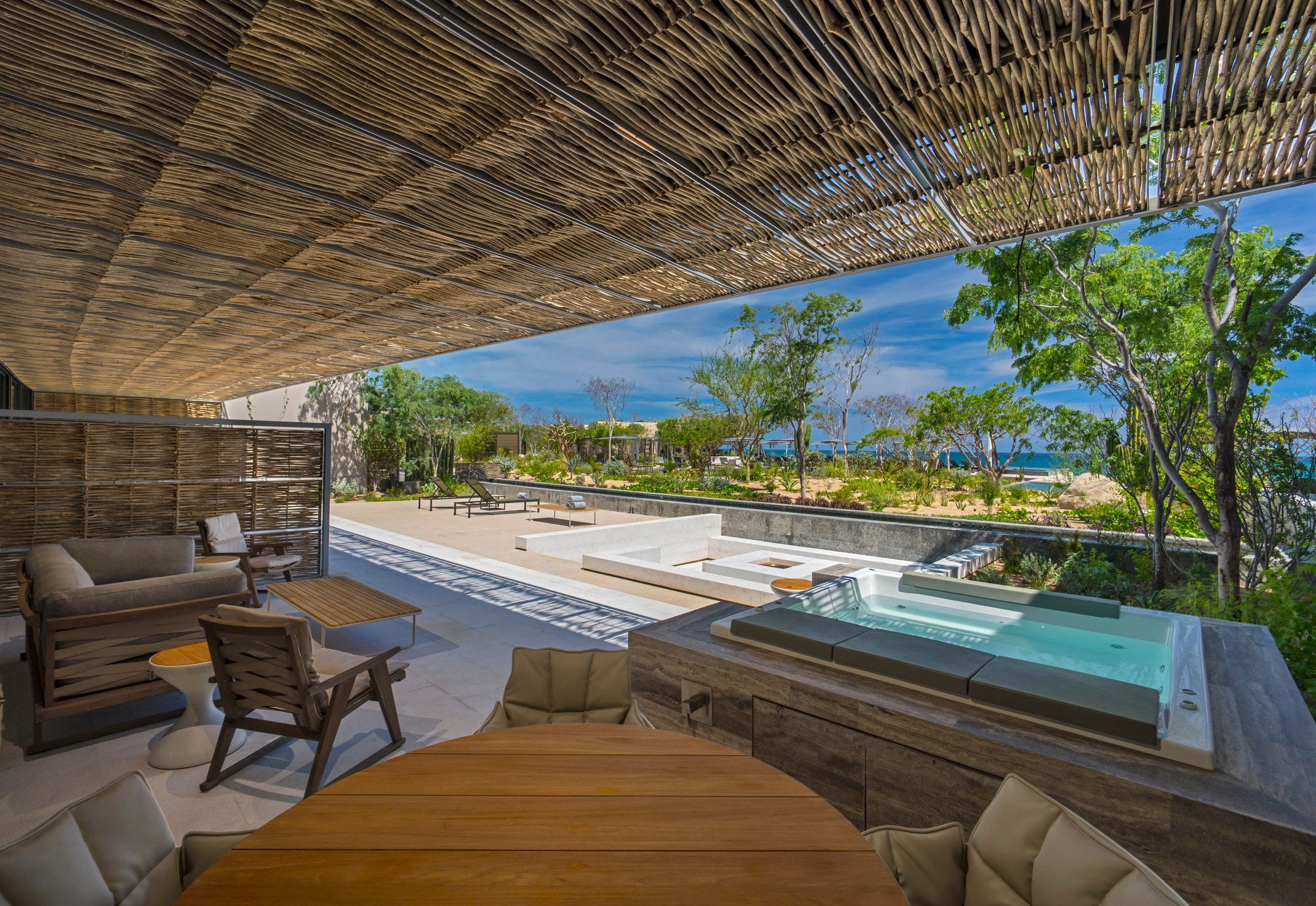 Outdoor living area with thatched ceiling with pool and ocean view