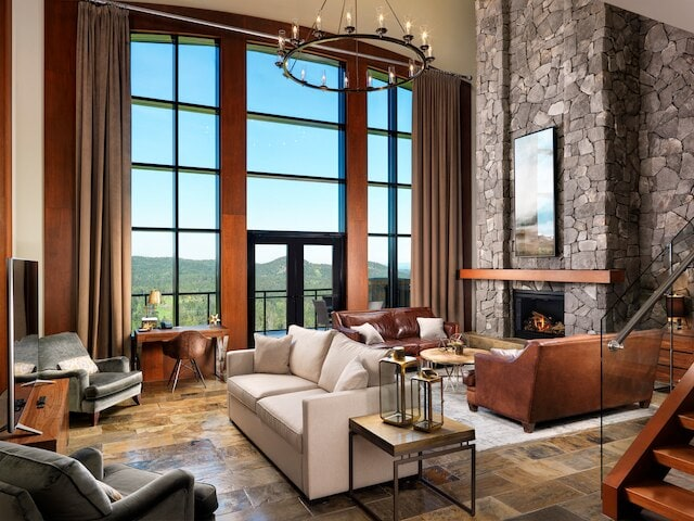 Large living area with stone fireplace and 2-story window wall with mountain views