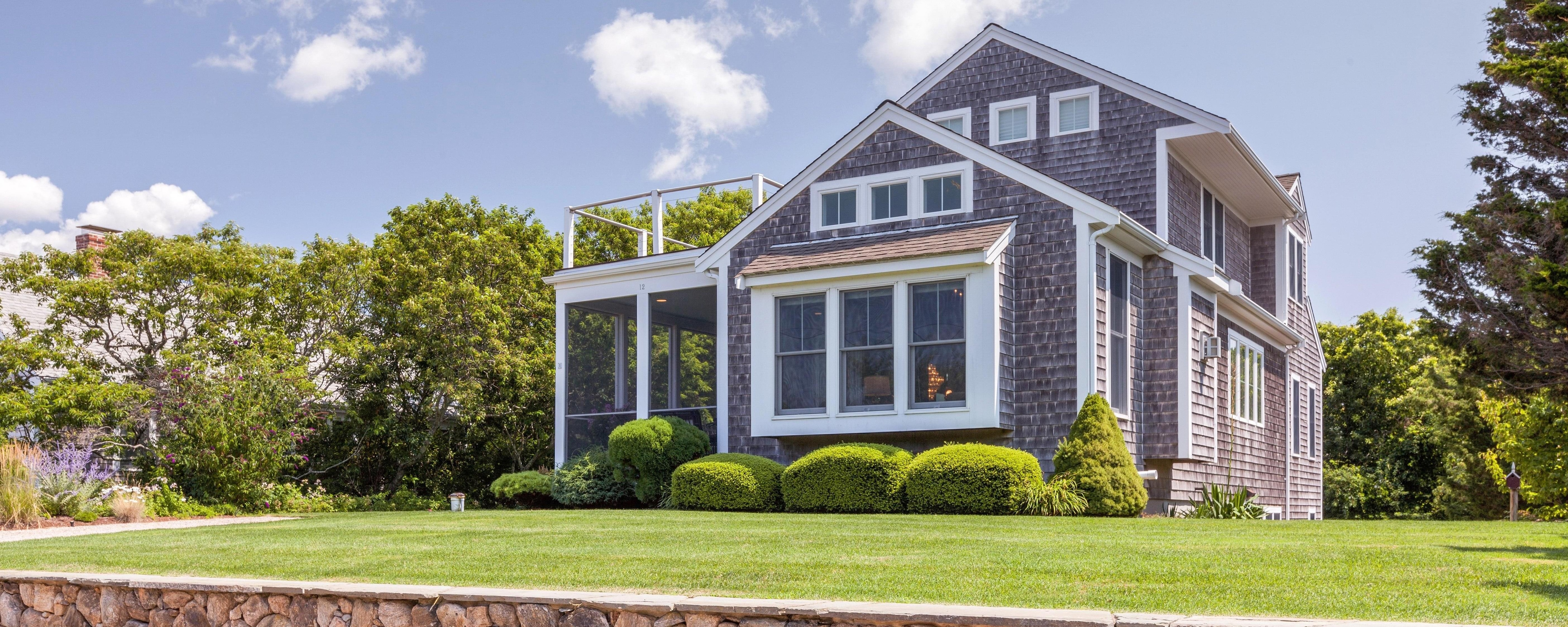 Charming, spacious gray cottage in Cape Cod with natural stone wall.