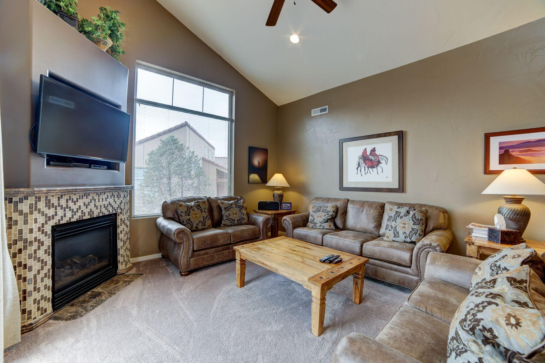 This cozy spacious living room offers plenty of comfortable seating, a large flat screen TV as well as great views and a gas fireplace!