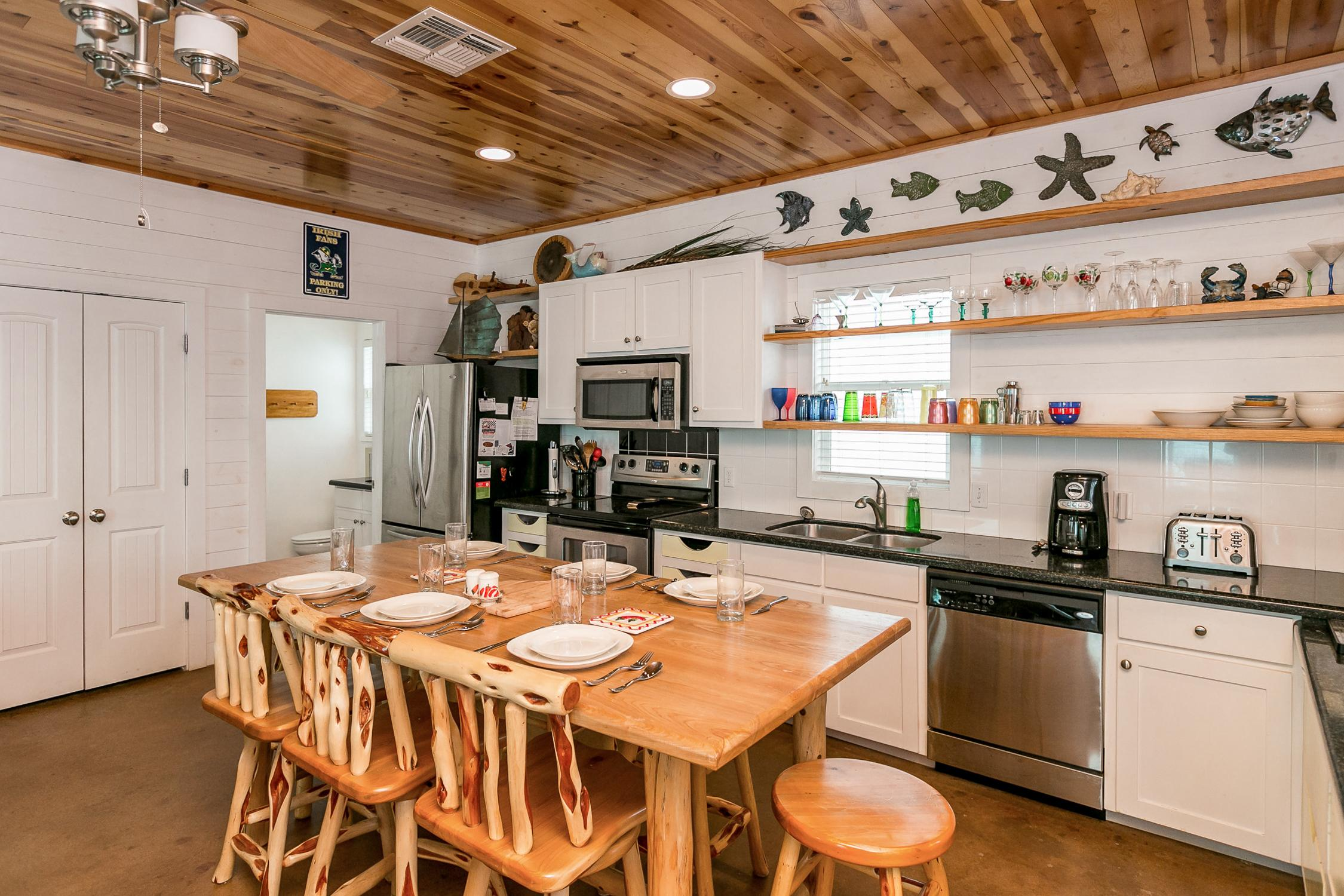 The kitchen is equipped with modern stainless steel appliances, open shelves, and even a small kegerator.