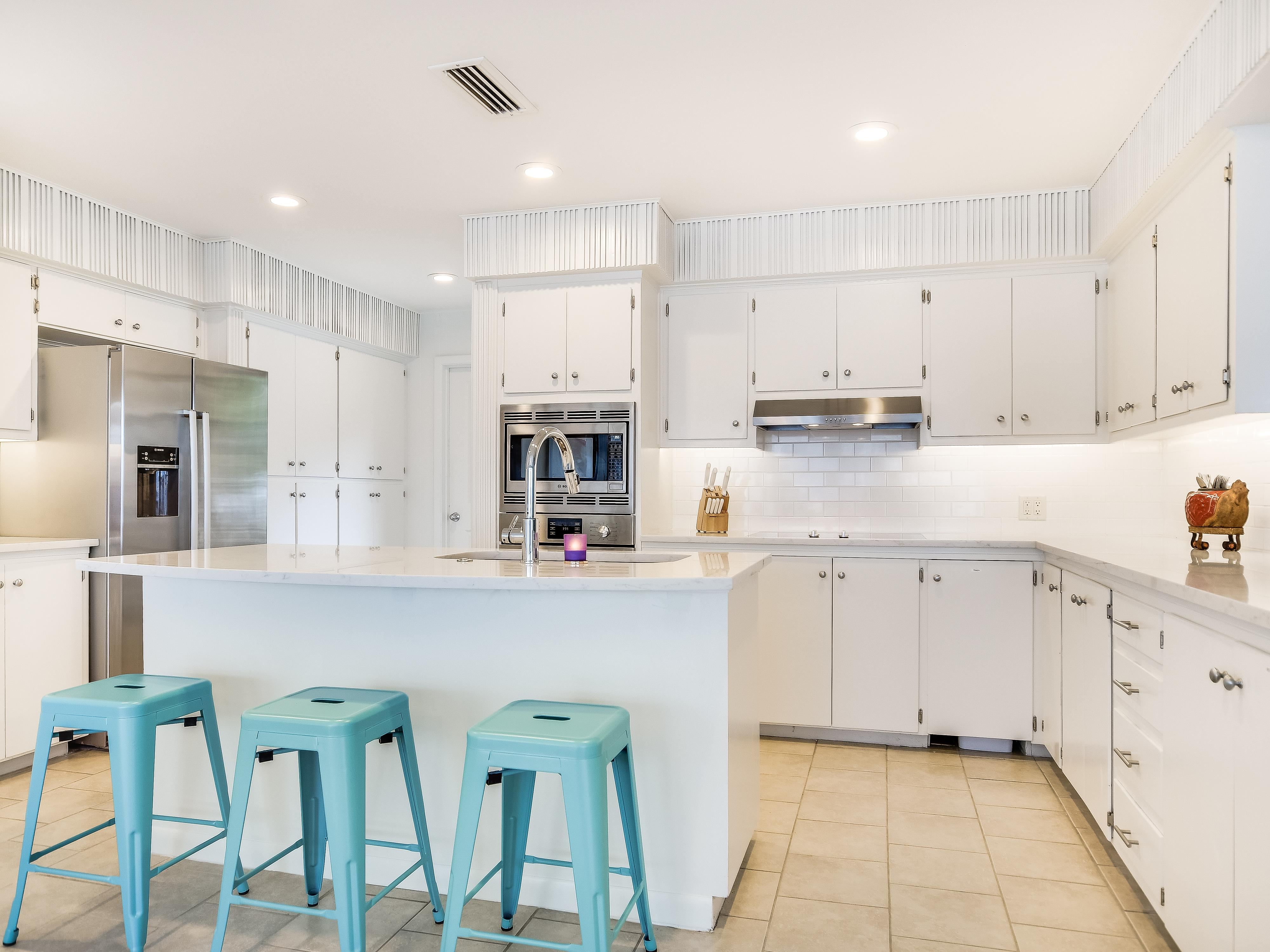 The bright white kitchen features stainless steel appliances and seating for 3 at the island.