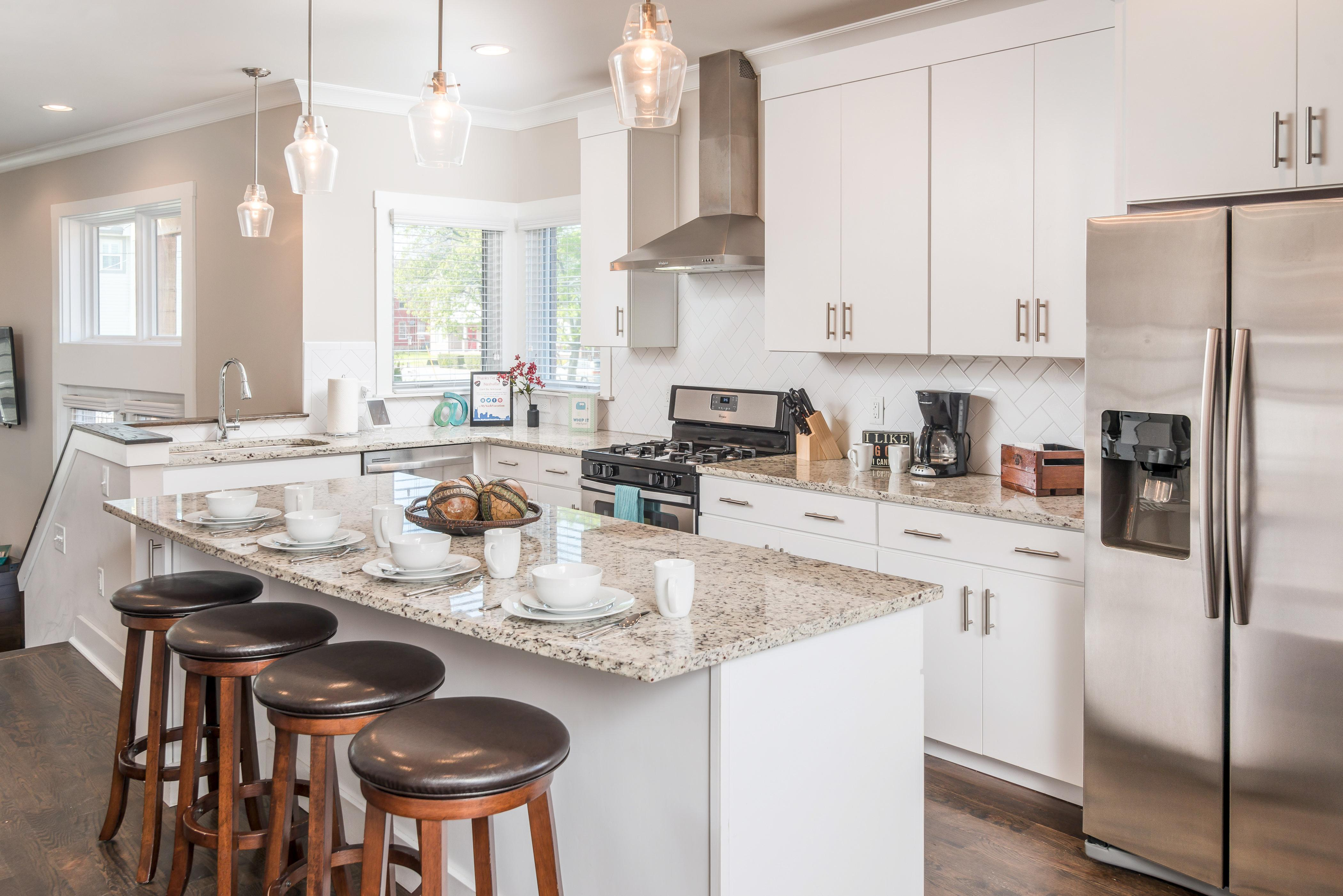 A chef's kitchen is full of luxury touches, including granite countertops, a gas range, and all new stainless steel appliances.