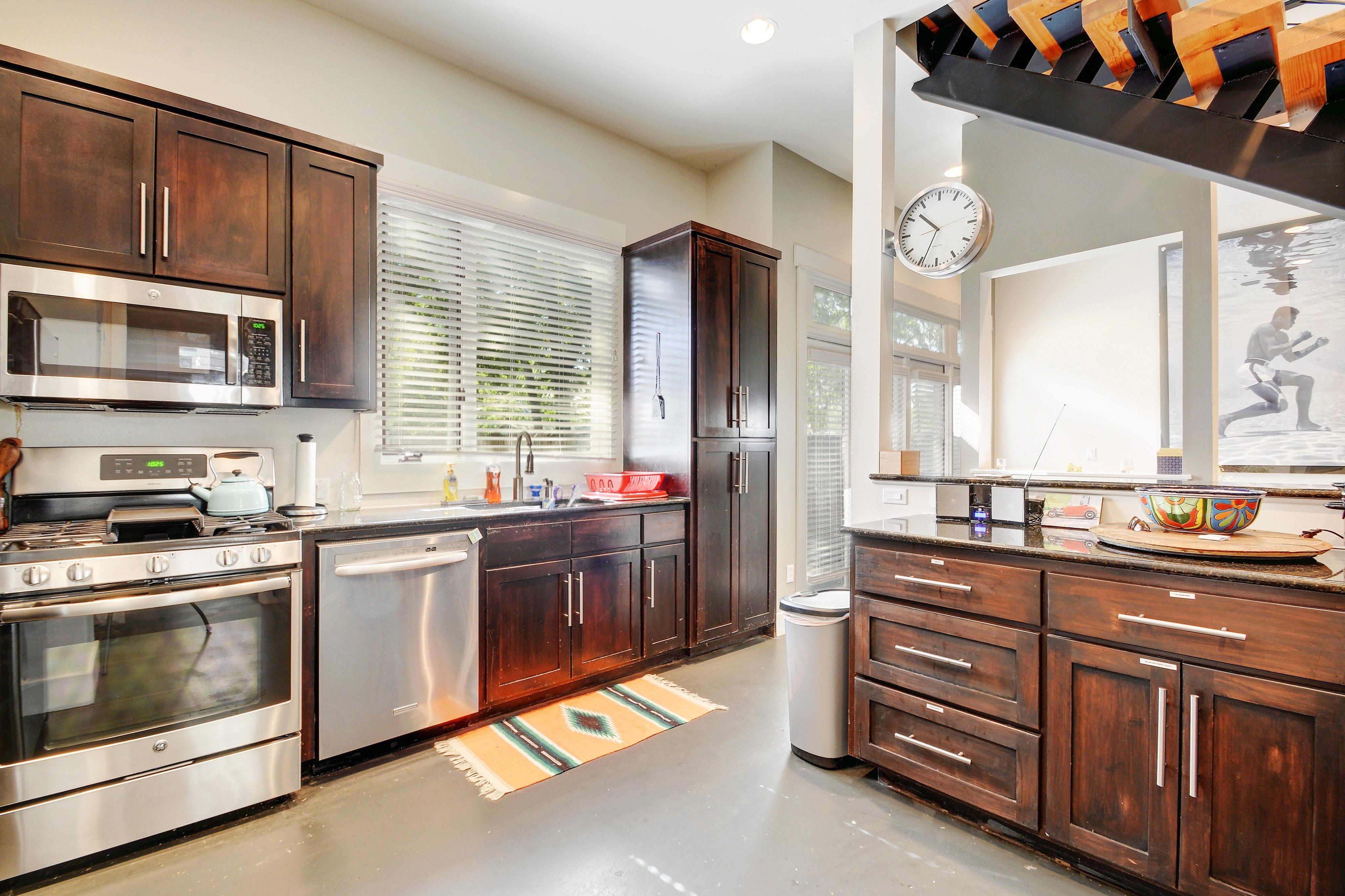 Granite countertops and all stainless steel appliances, including dishwasher, range, and fridge.