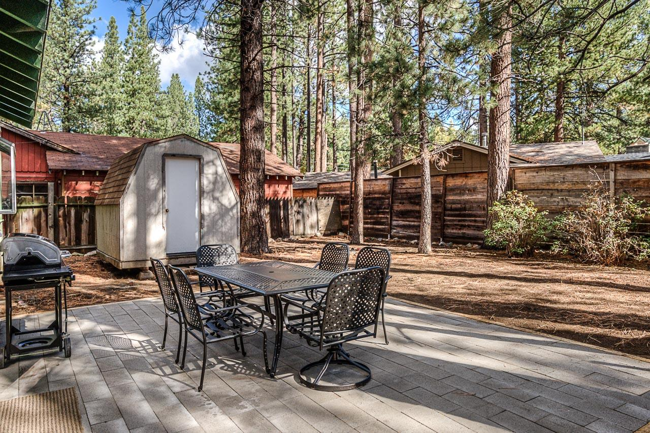 A secluded outdoor patio is shaded by pines trees. (Please note: Outdoor wood-burning fires and charcoal grills are prohibited per local ordinances.)