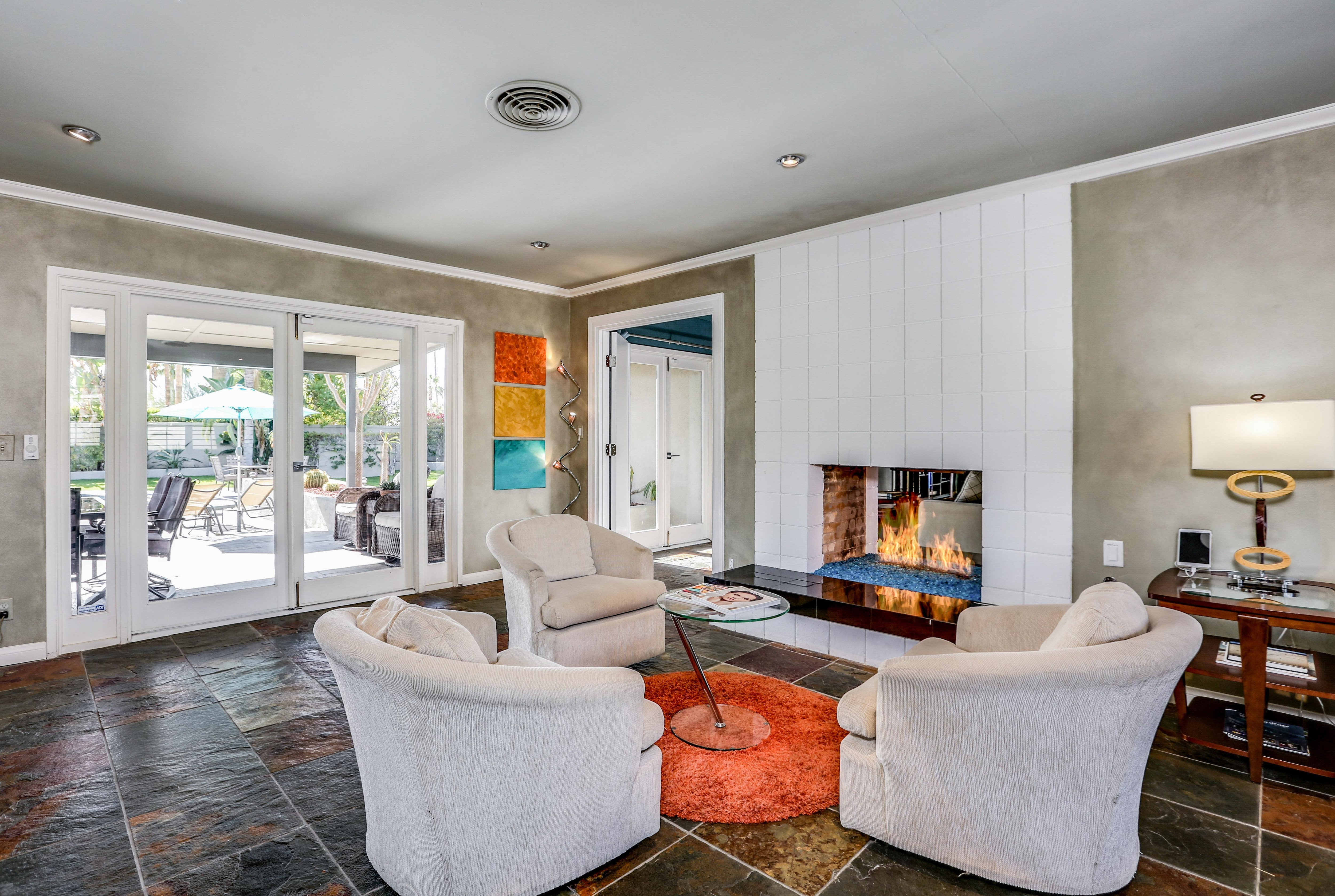 Relax on 3 comfy armchairs next to the flickering fireplace.