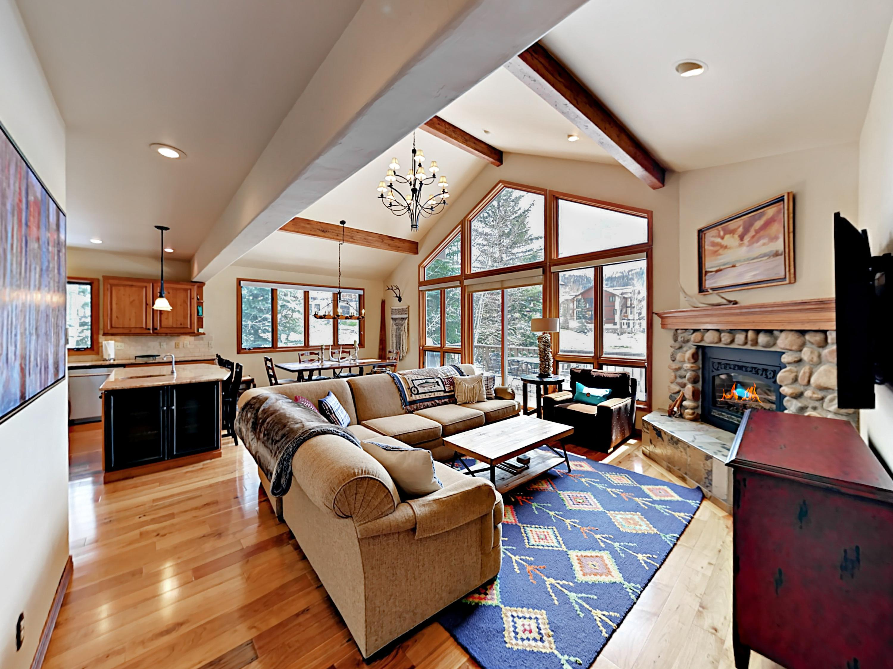 In the living room, natural light pours through floor-to-ceiling picture windows and glass doors leads to the patio.