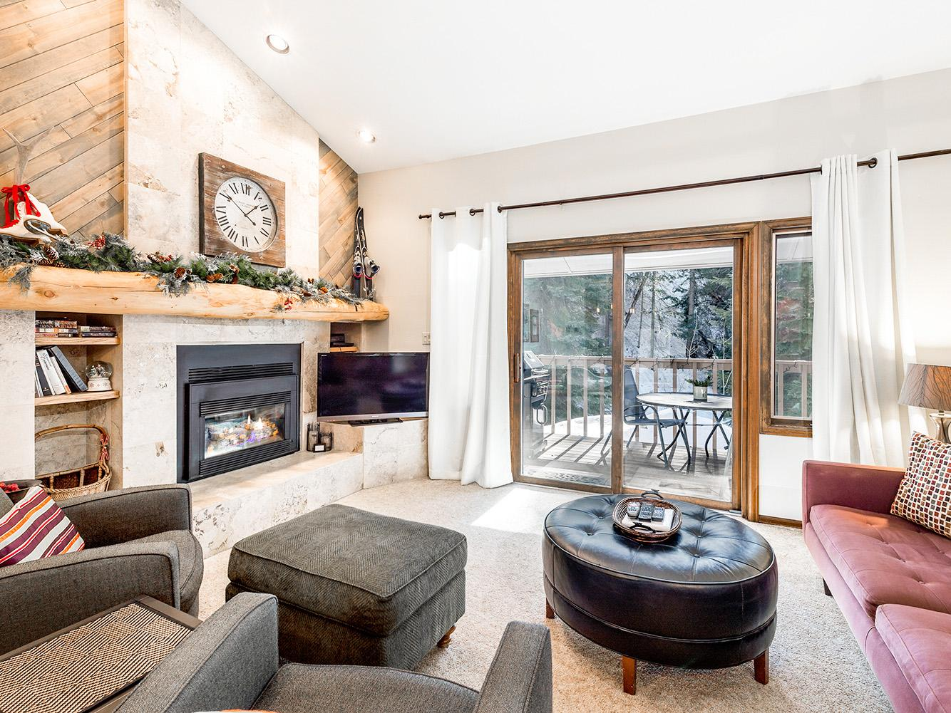 A comfortable living area features vaulted ceilings, rustic timber accents, and vintage ski decor.