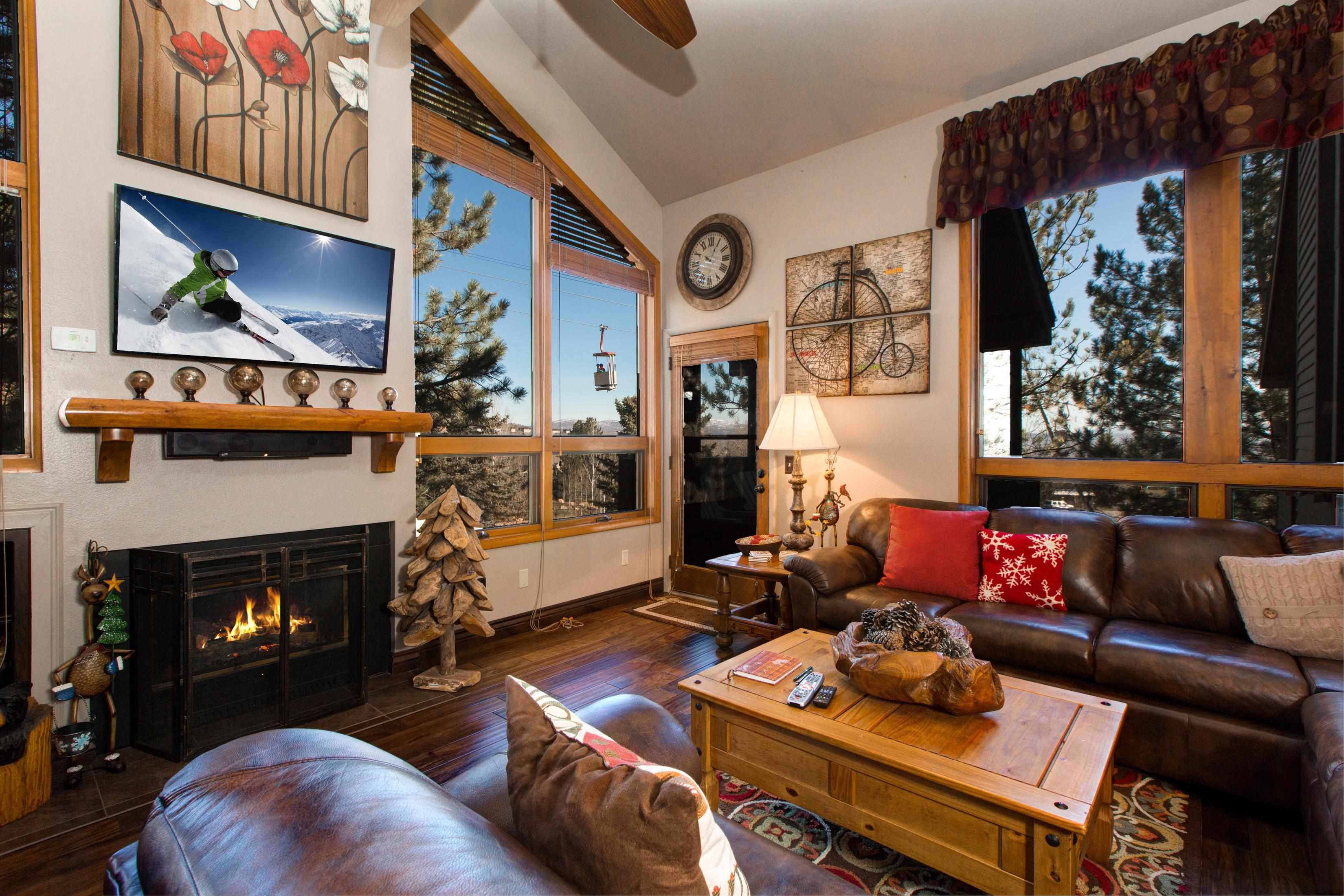 Welcome to Park City! Cozy and classic living area with a flat-screen TV and wooded views through large windows.