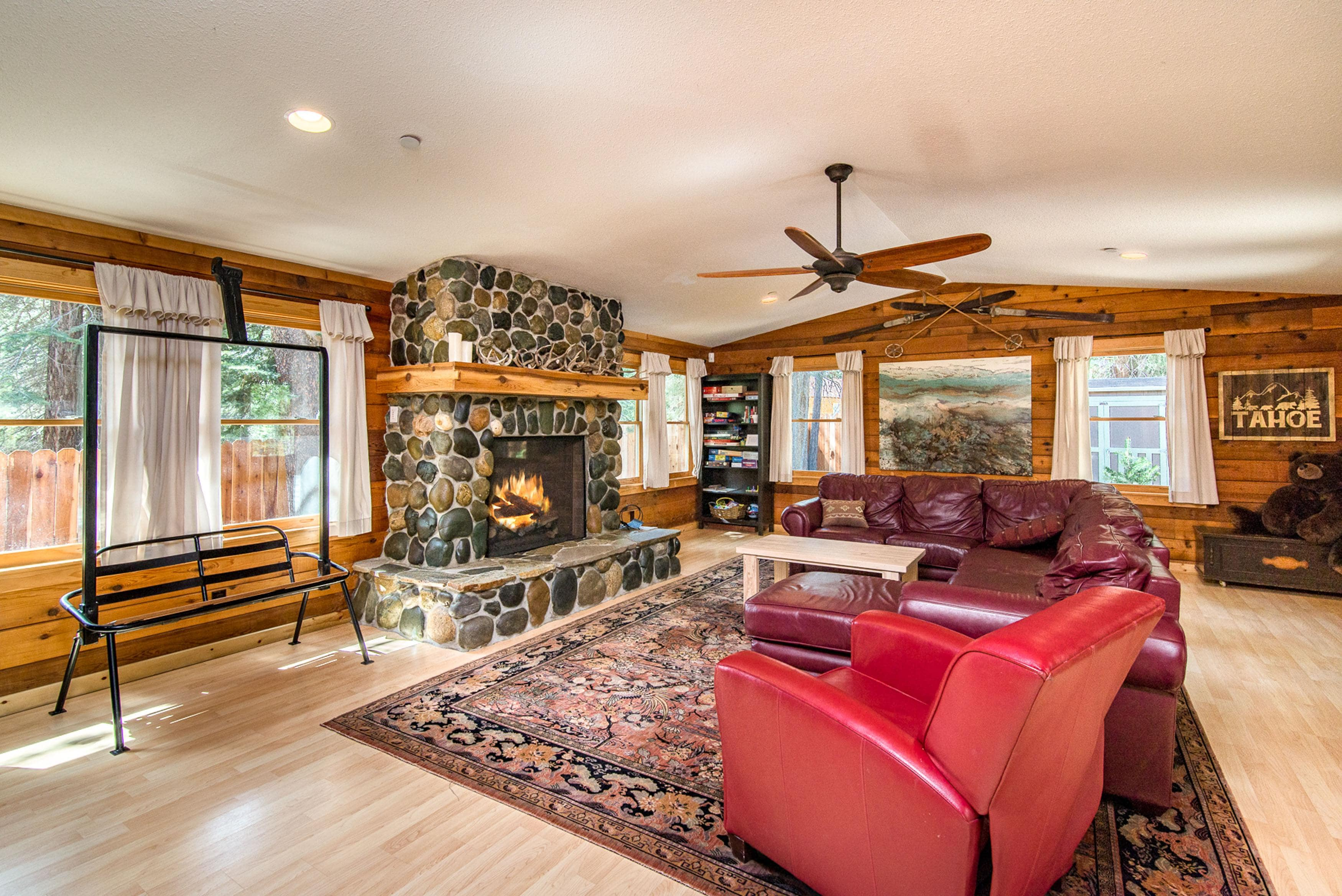 The family room provides comfortable seating around a majestic stone fireplace.