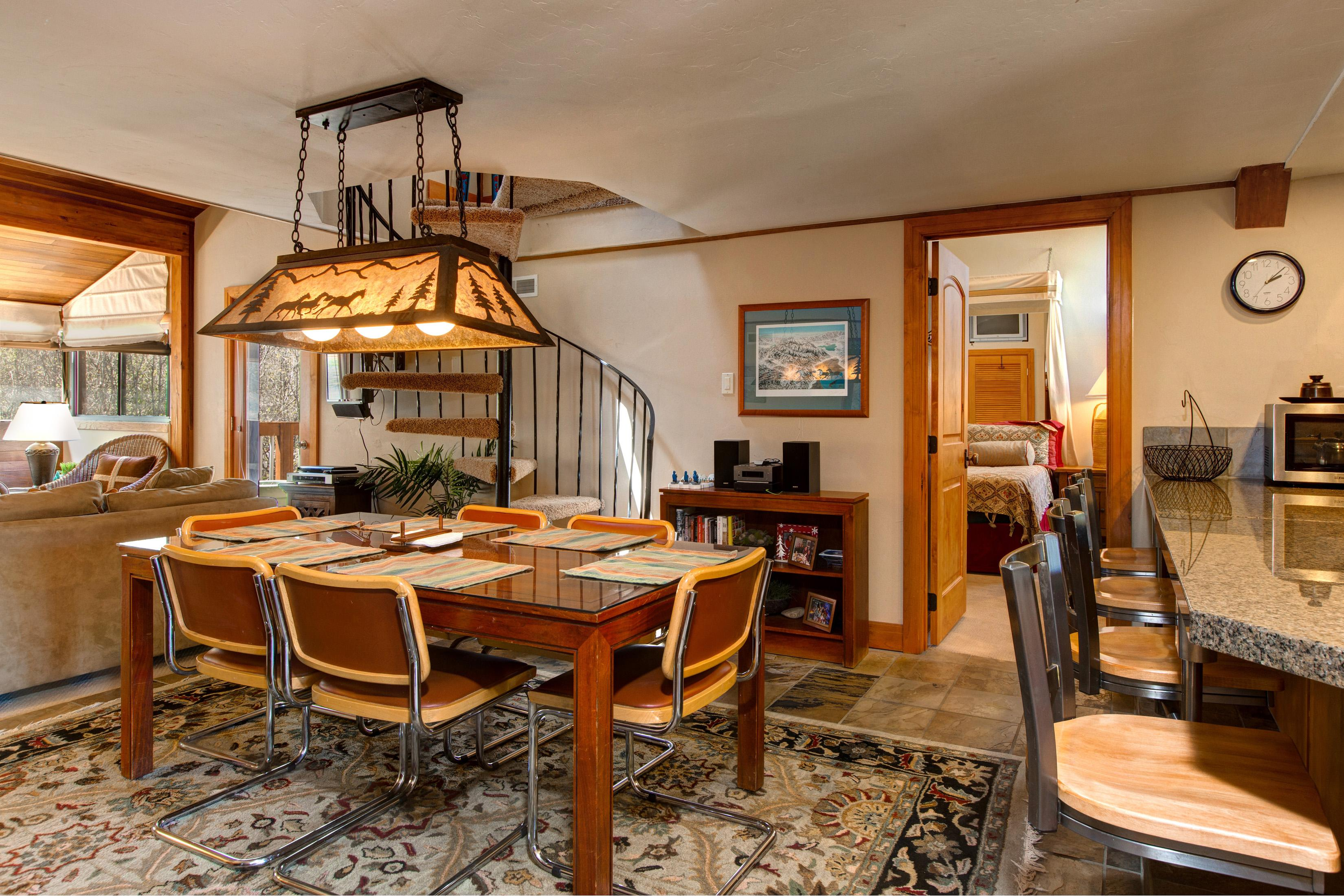 The unique dining area features a lovely wood table, 6 chairs, and a beautiful chandelier.