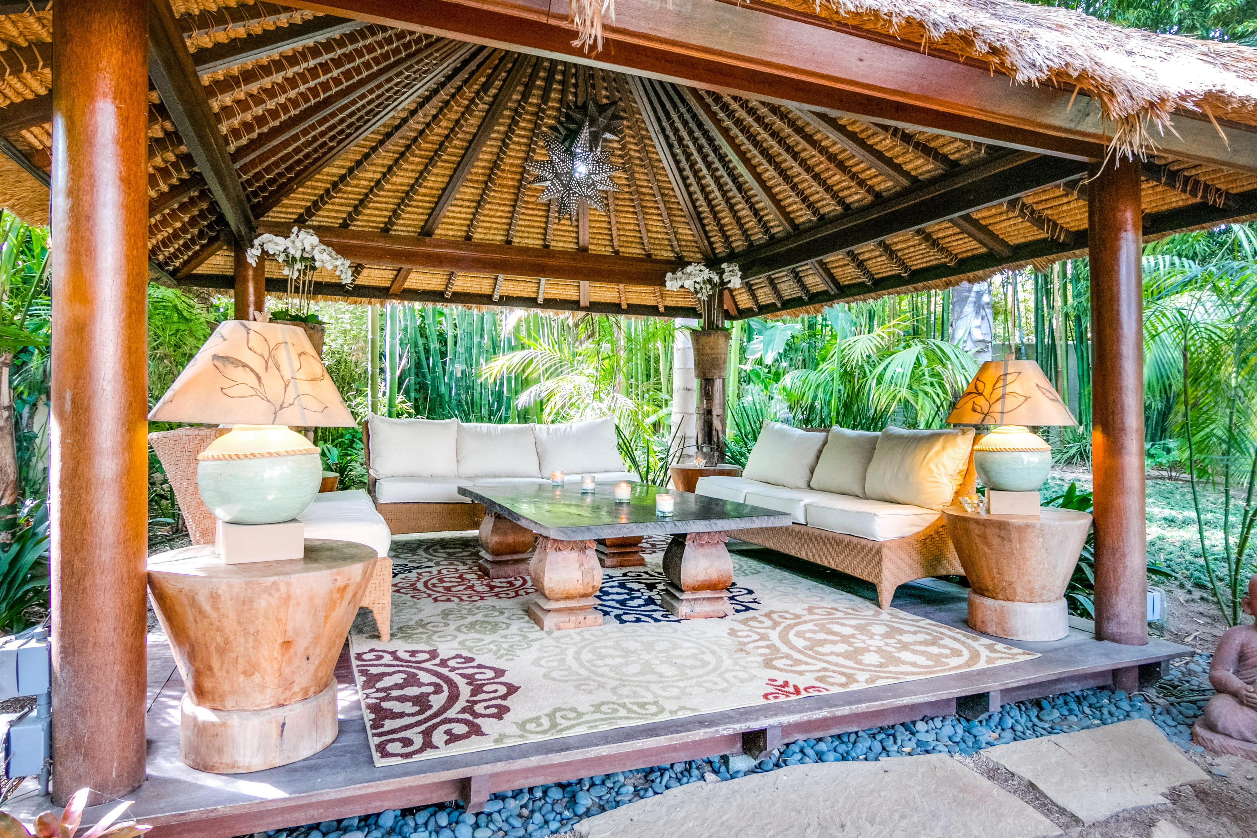 Get cozy in the outdoor living room, sheltered under a thatched-roof cabana.