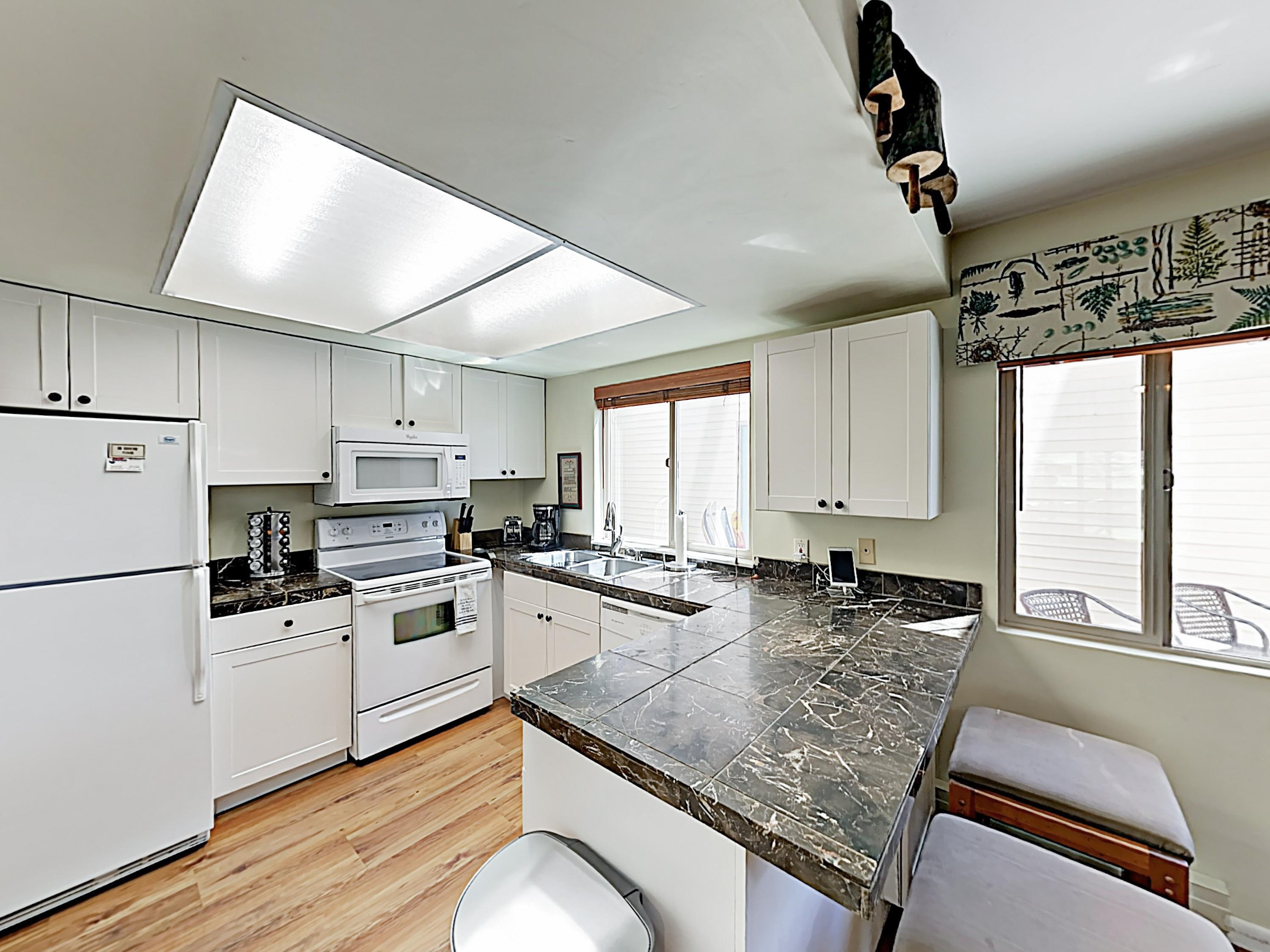 Granite countertops and quality all-white appliances outfit the kitchen.