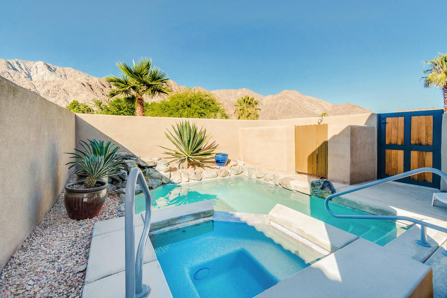 Welcome to La Quinta! The vacation-ready backyard includes a private pool, palm trees, and dramatic mountain backdrop.