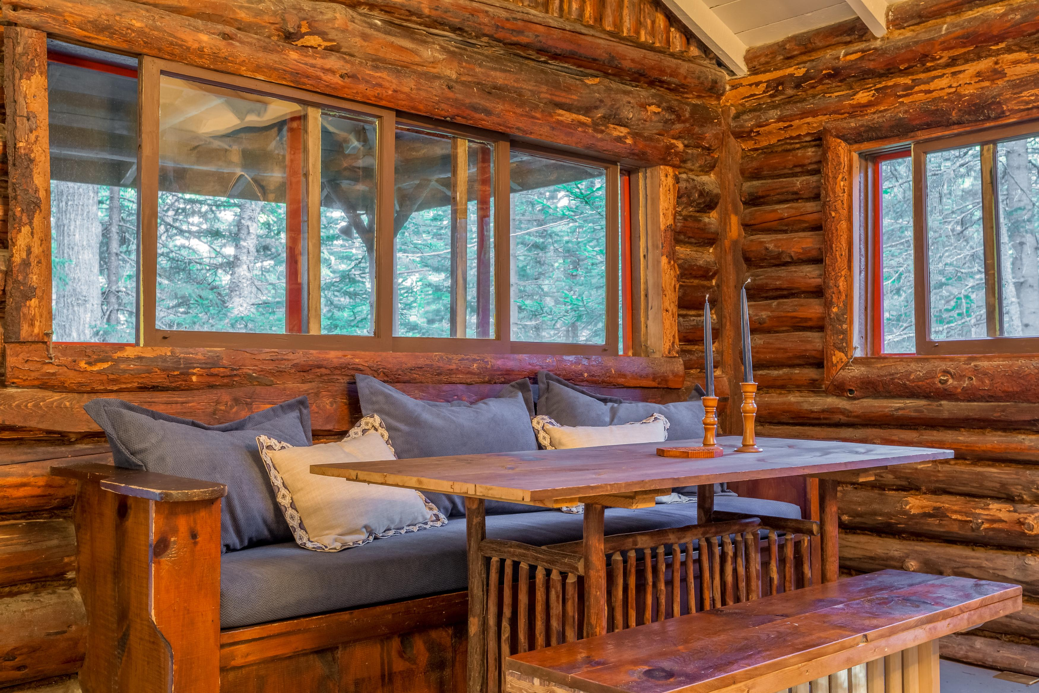Stunning log walls surround the comfortable dining area.