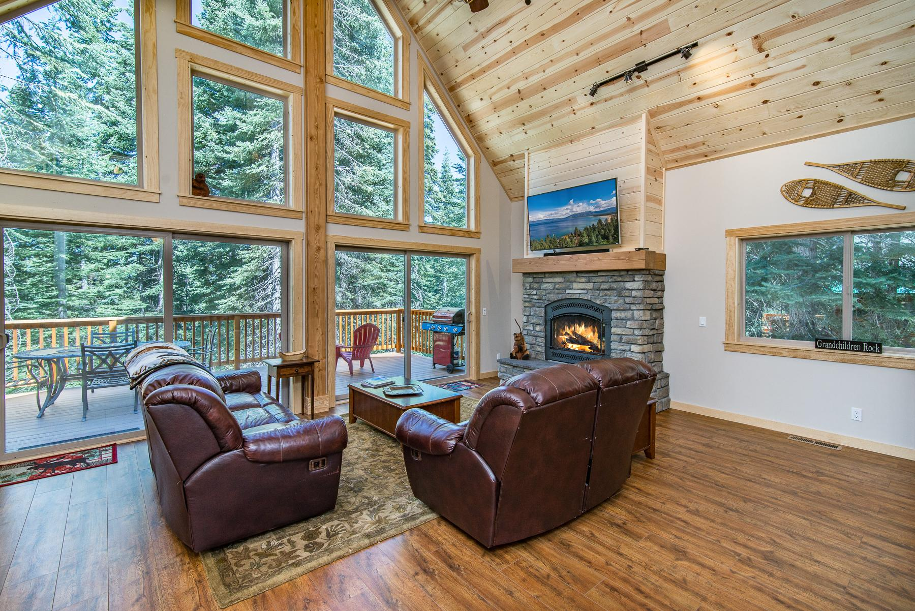 Floor-to-ceiling windows showcase lovely woodland views in the living area, where a gas fireplace with stone surround provides a warm vibe.