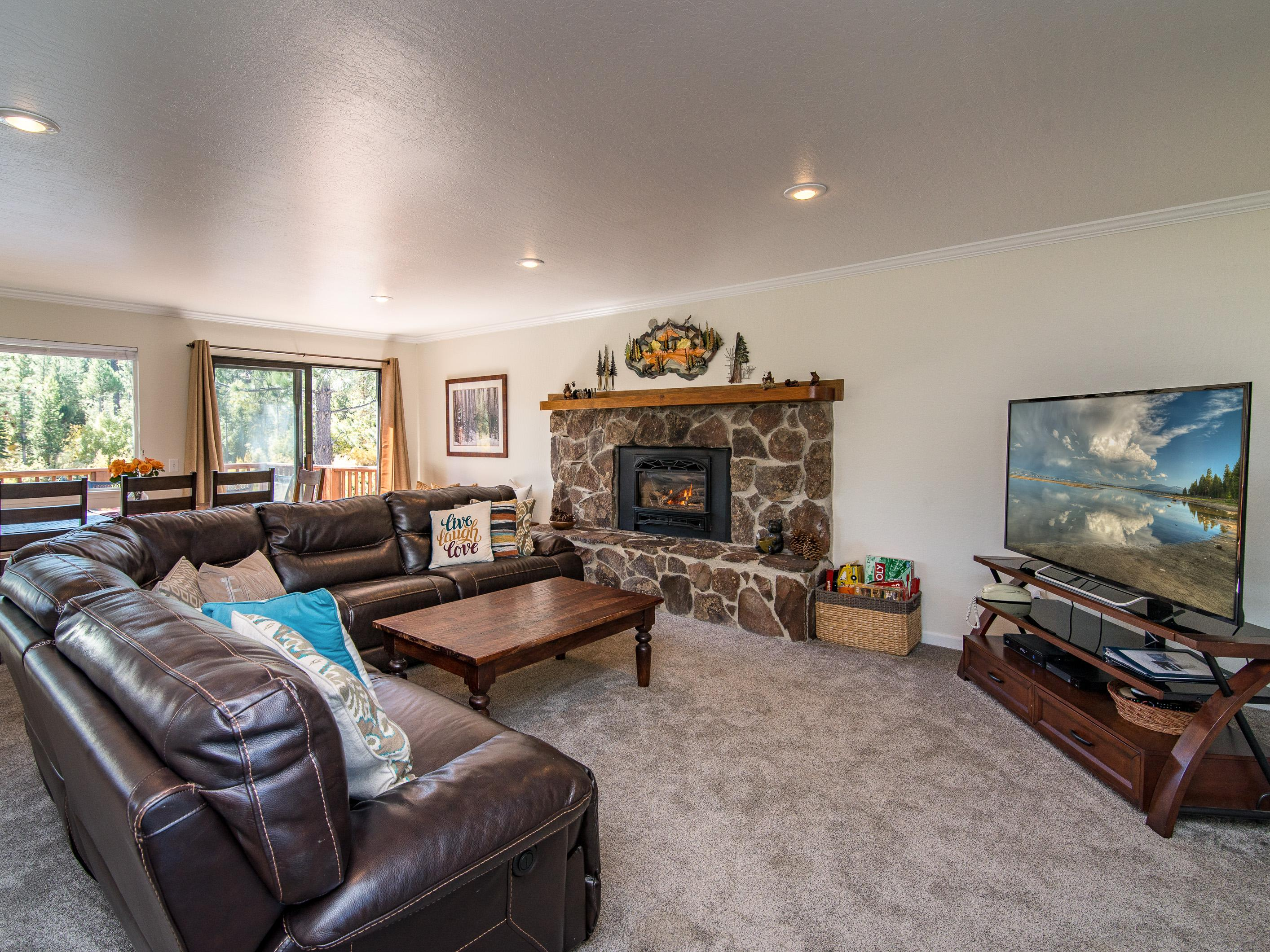 Gas fireplace with stone surround, plush leather seating, and extra-large flat screen TV in living room.