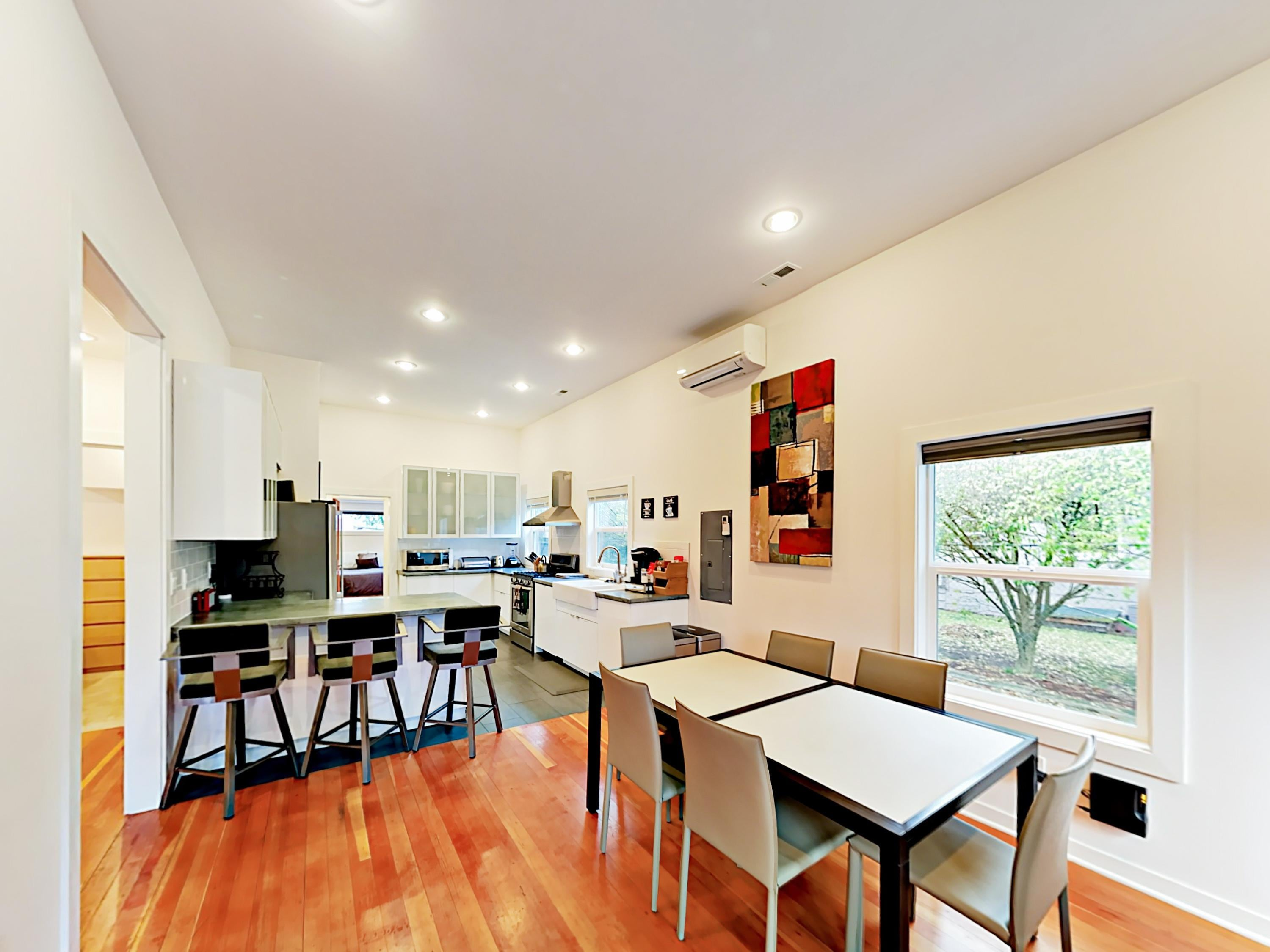 The open-concept living, dining, and kitchen is detailed with beautiful hardwood floors.