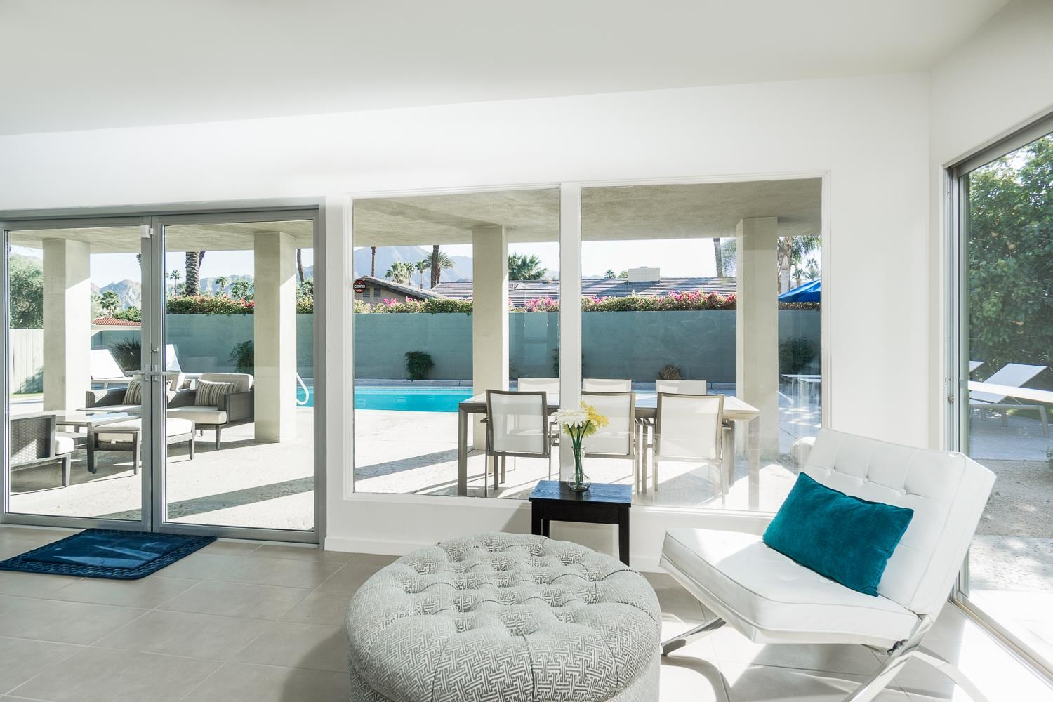 The living room invites you to lounge on a white leather sofa amid pool views