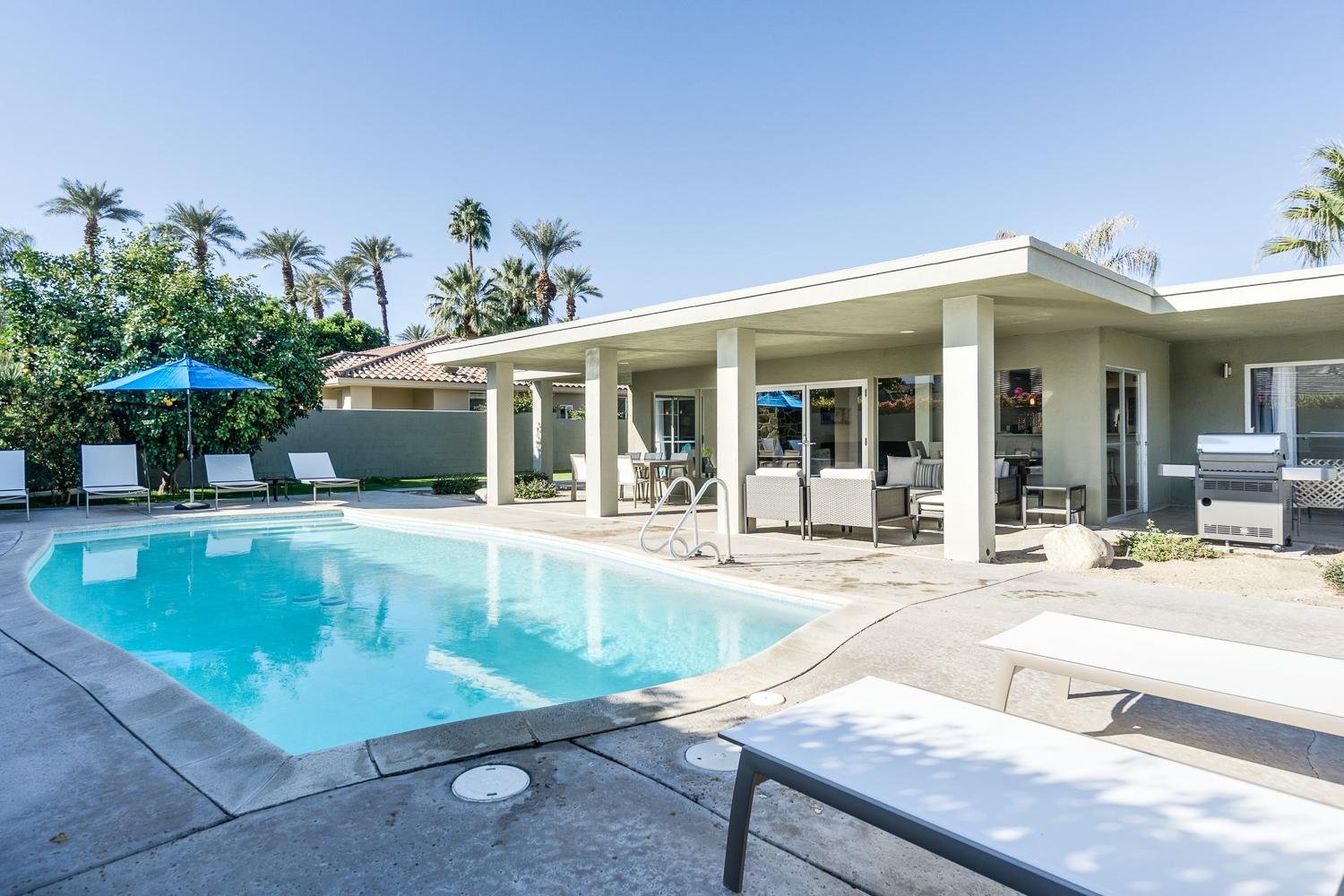 Welcome to Palm Springs! Our corner lot location features a lush yard and pool outside