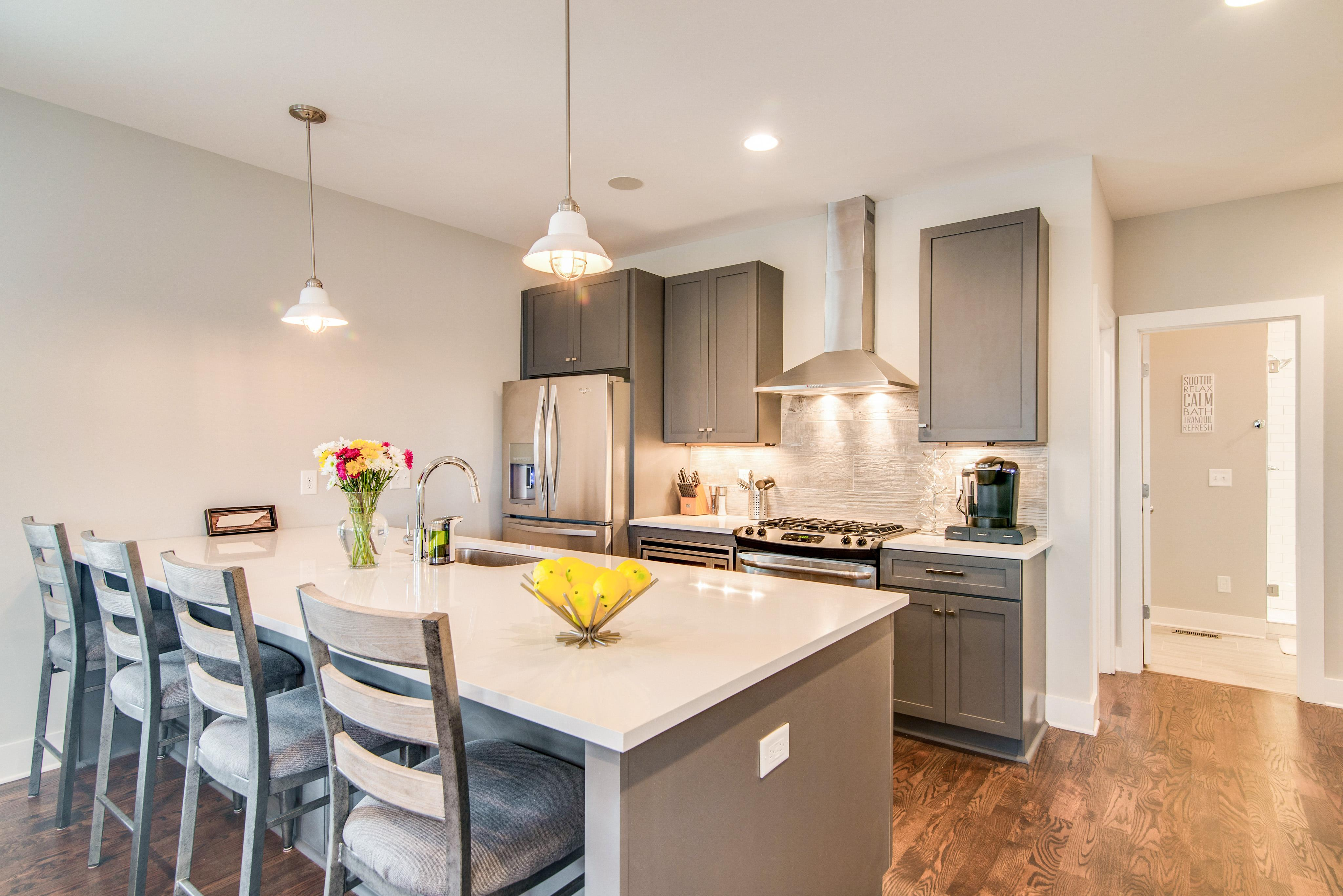 Channel your inner chef in the gourmet kitchen featuring white quartz counters and trendy grey cabinets