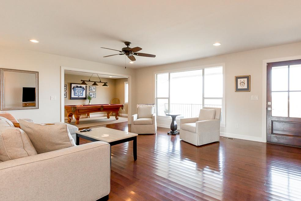 The open living room features a sectional and 2 armchairs.