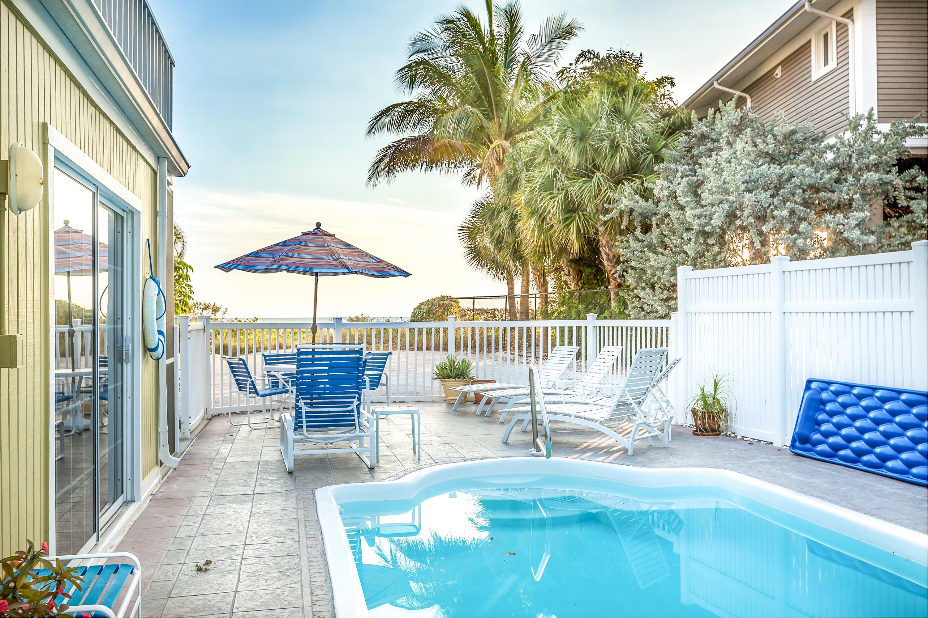 Swim in a private pool with loungers, an outdoor dining set, and a Gulf view.
