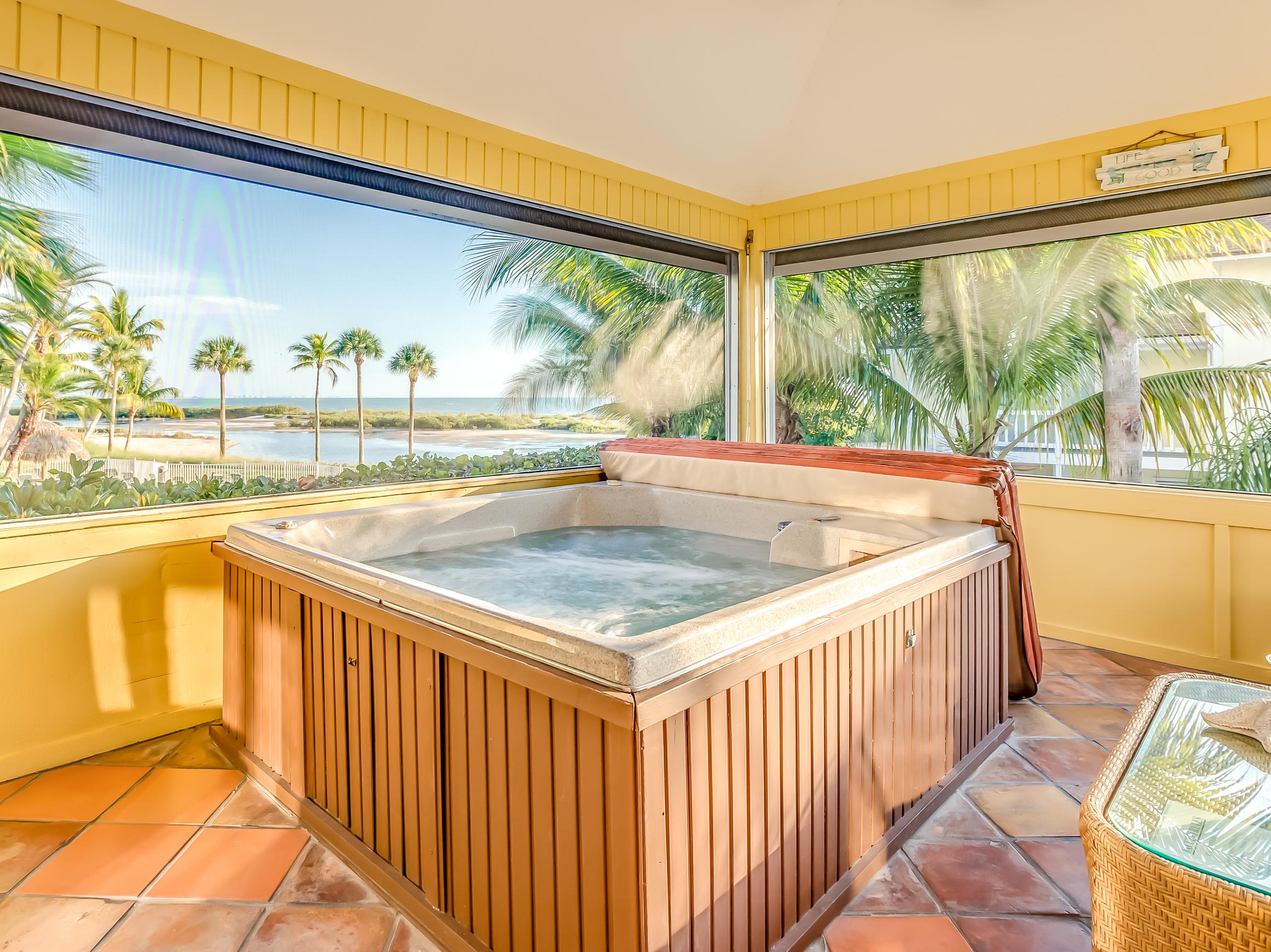 The screened lanai offers plenty of seating and a hot tub with views of the estuary.