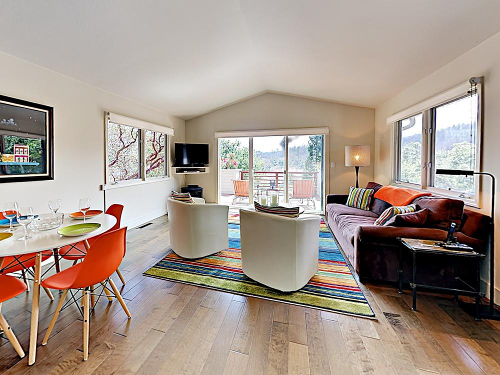 Vibrant colors and wood floors in the cottage living area, with sliding glass doors leading to the mountain-view deck.
