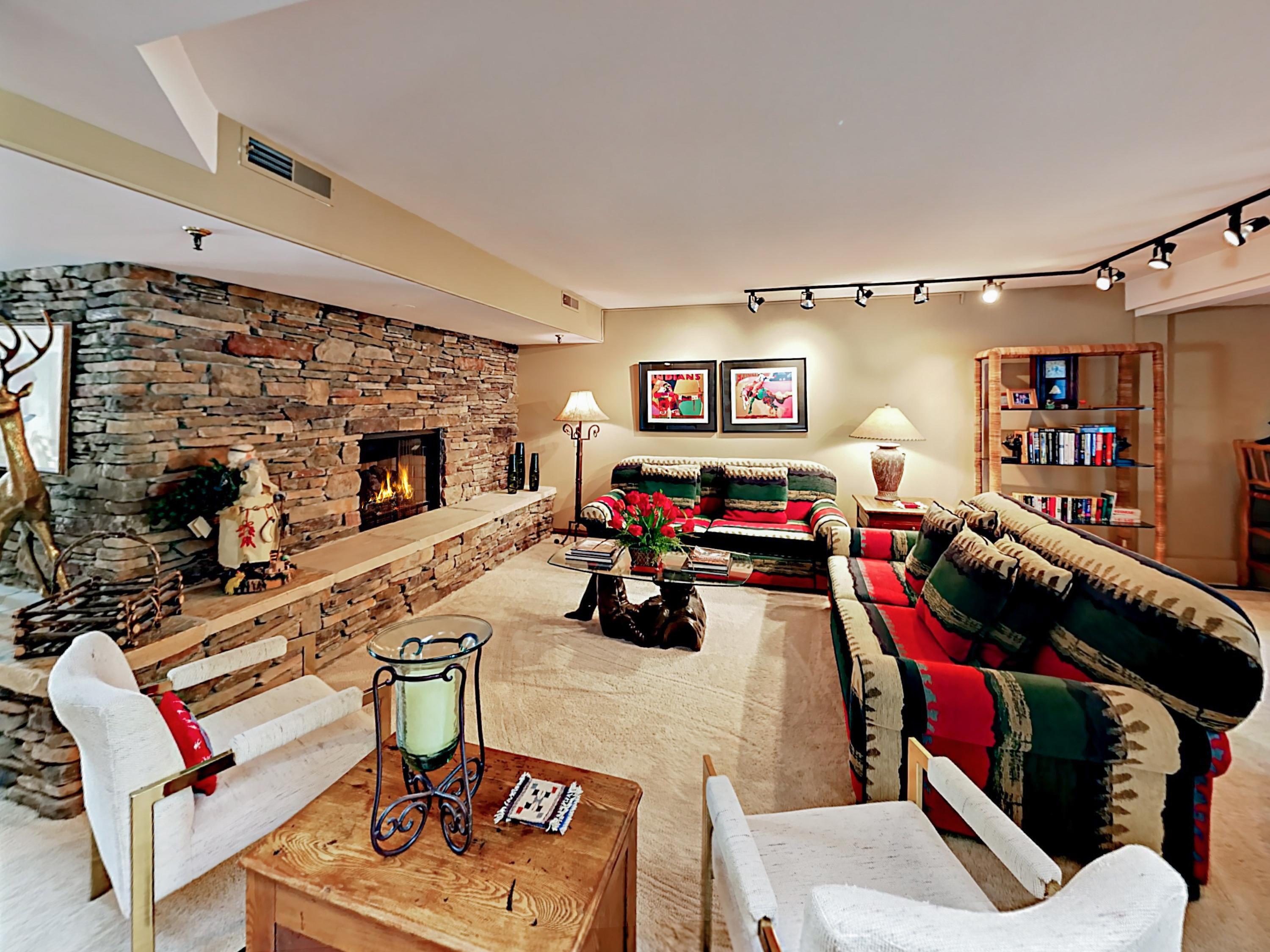 Stretch out on 2 sofas and armchairs in the second living room next to the flickering fireplace.