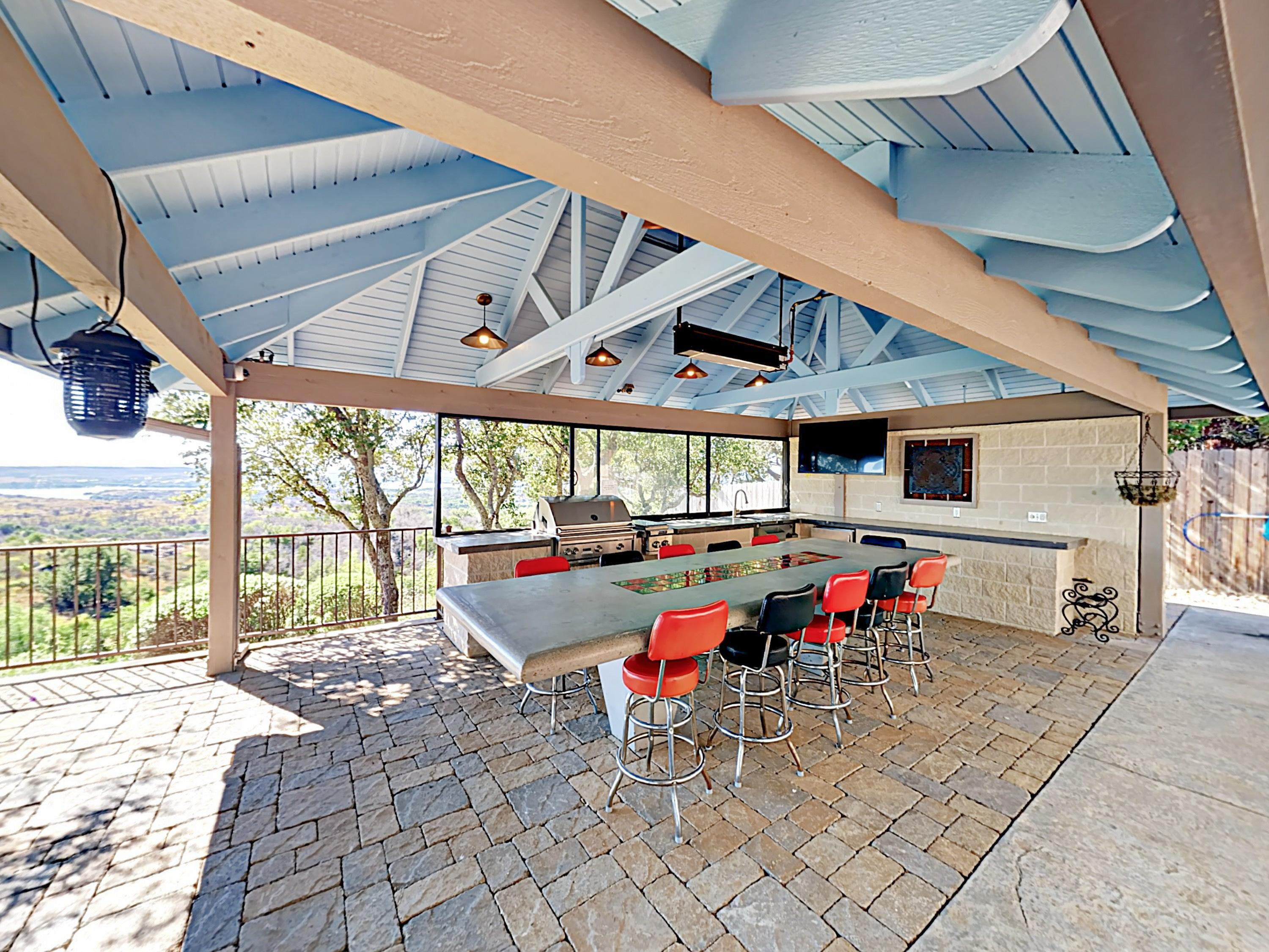 "This impressive outdoor space features a stainless steel gas grill, double burner, mini fridge, 11-seater dining table, and 55"" flat screen TV."