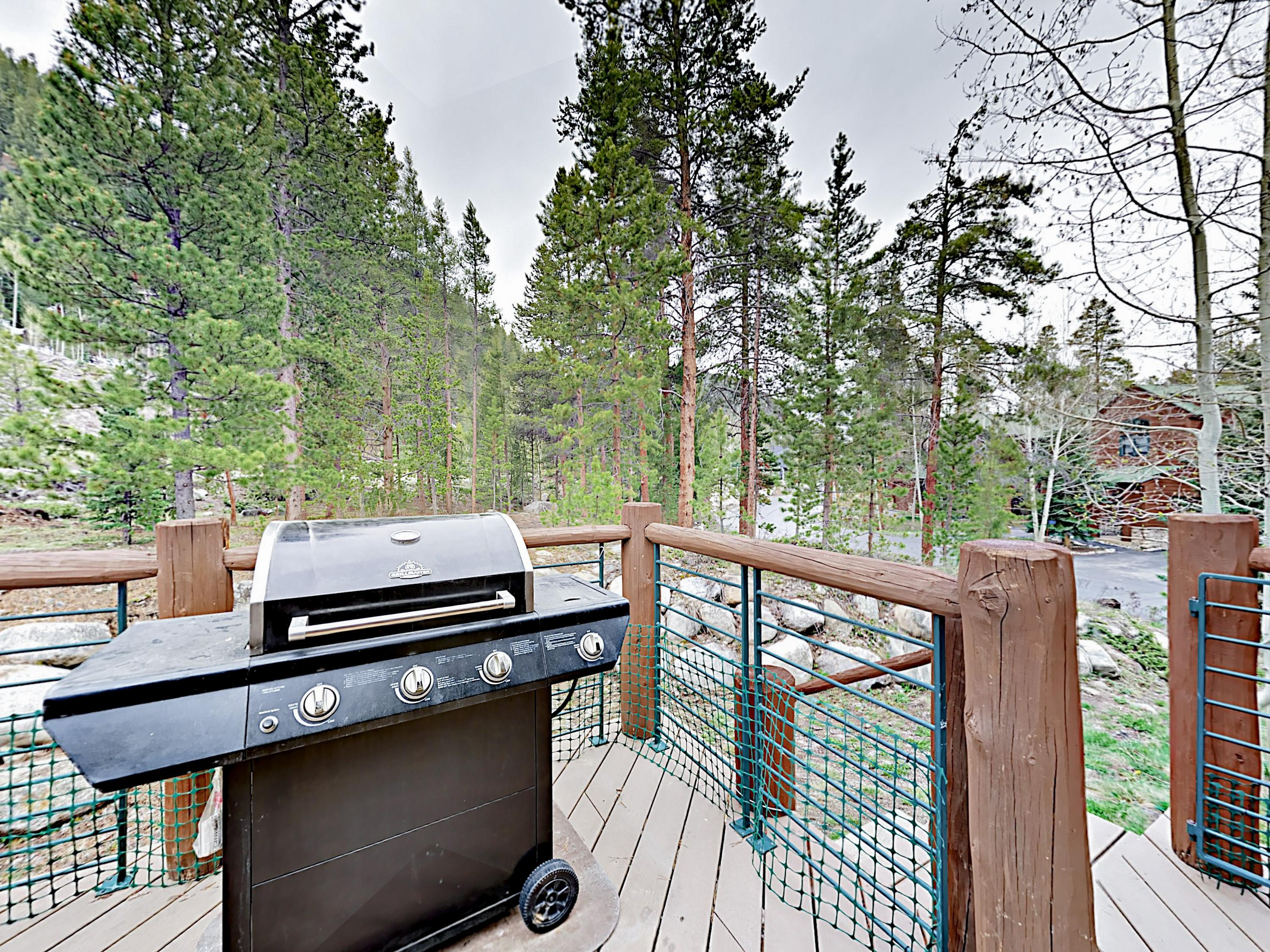 Grill on a forested deck with wooded views and seating for four.