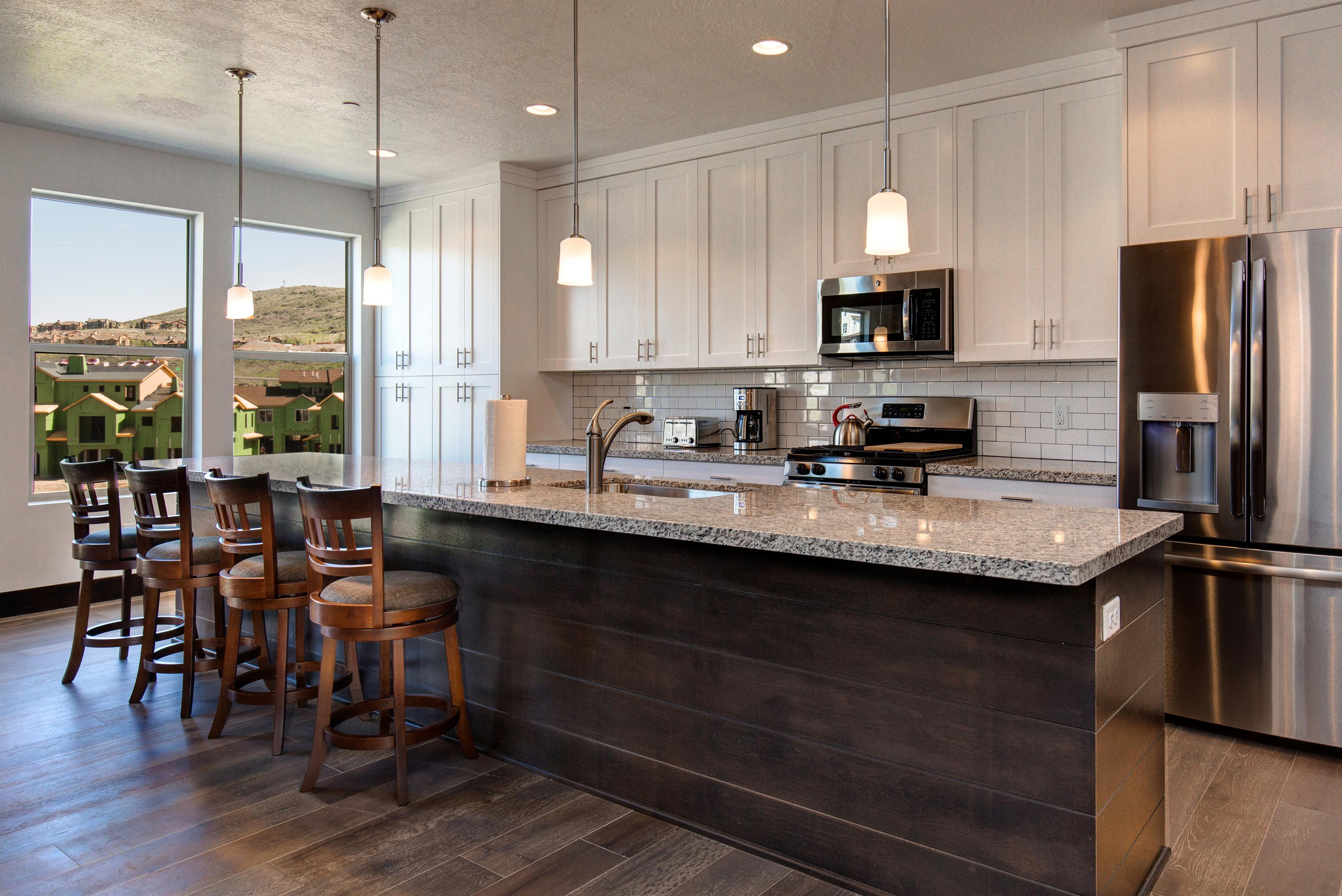 The gourmet kitchen features stainless appliances, granite counters, and a gas range.