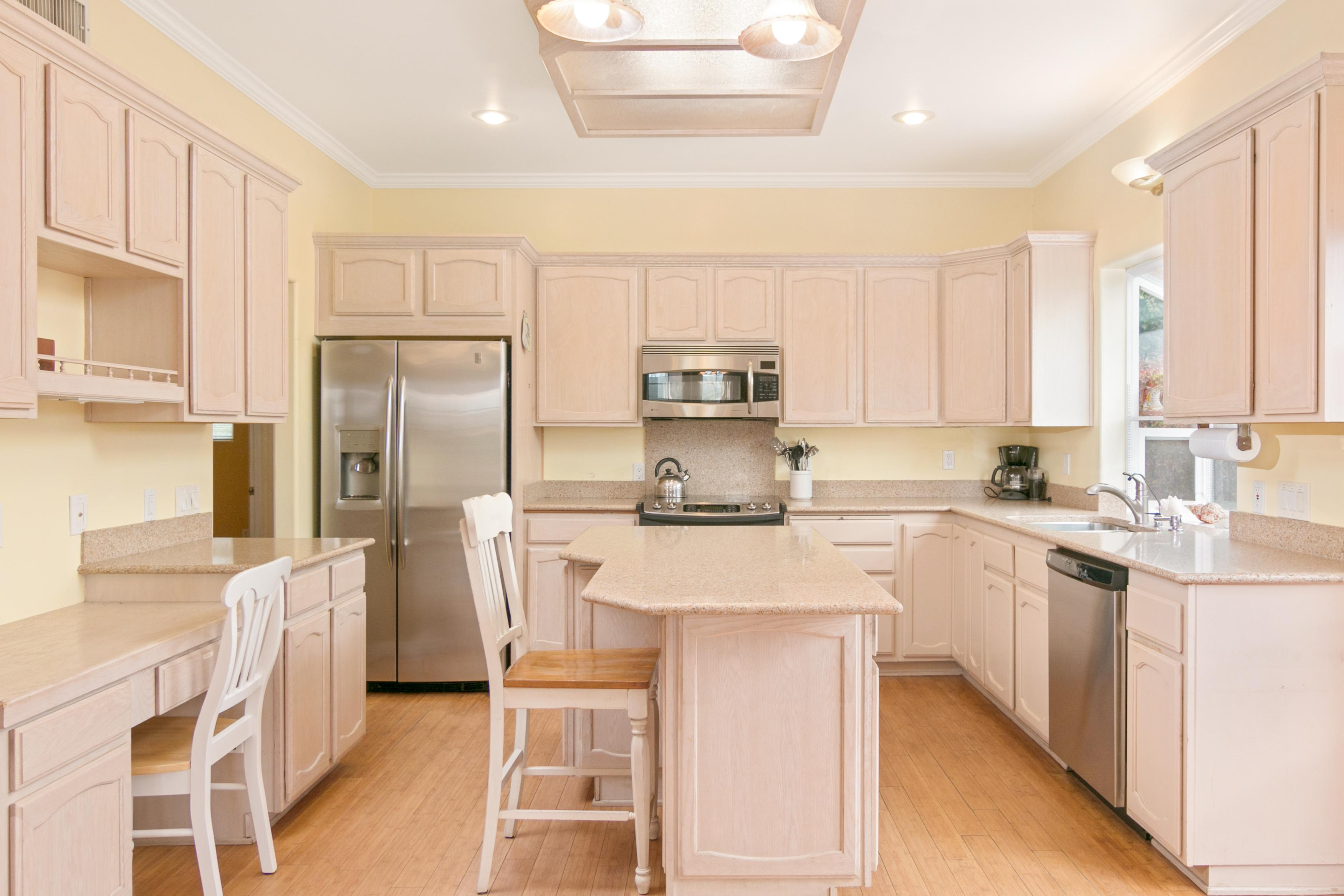 The kitchen with a center island, granite countertops and stainless steel appliances