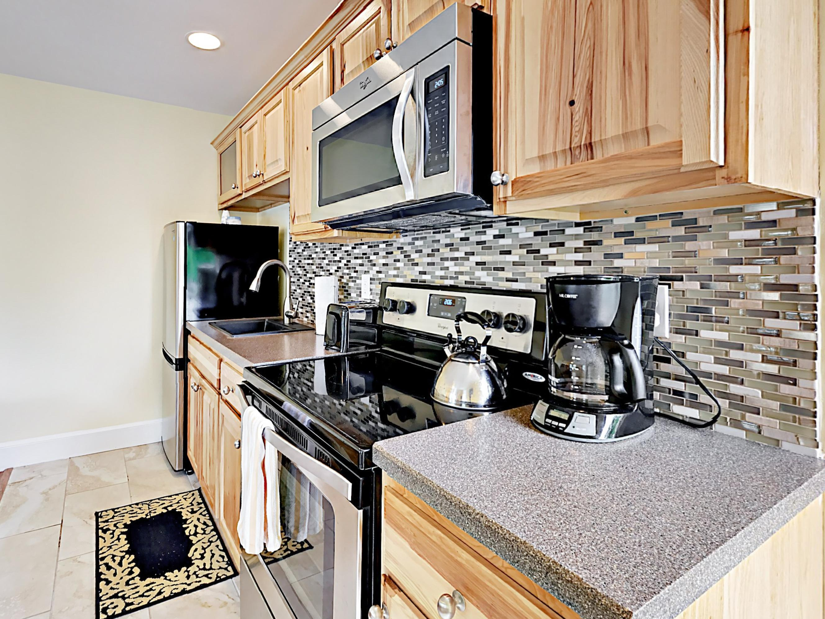 The kitchen includes a stainless steel fridge/freezer, stove/oven, and microwave