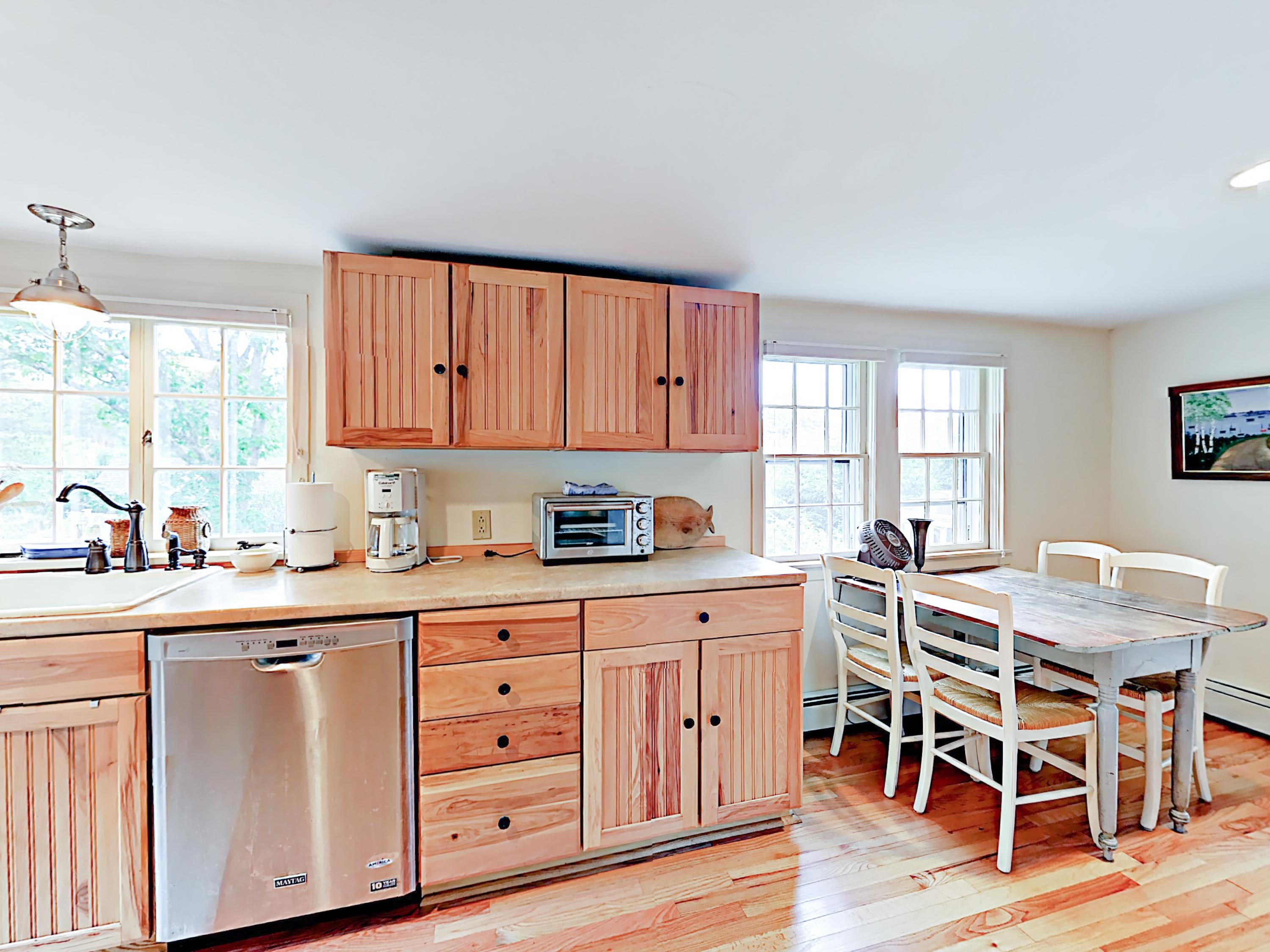A newly remodeled kitchen boasts glowing hardwood floors, galley-style cooking, and offers plenty of sunlight.