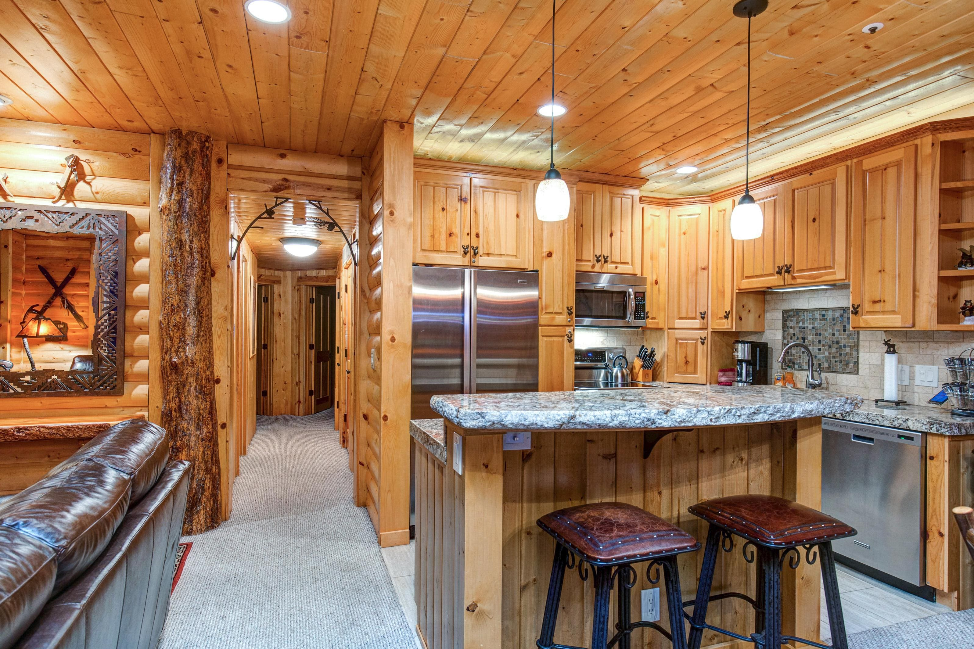 The fully equipped kitchen features granite countertops and stainless appliances, including double ovens.