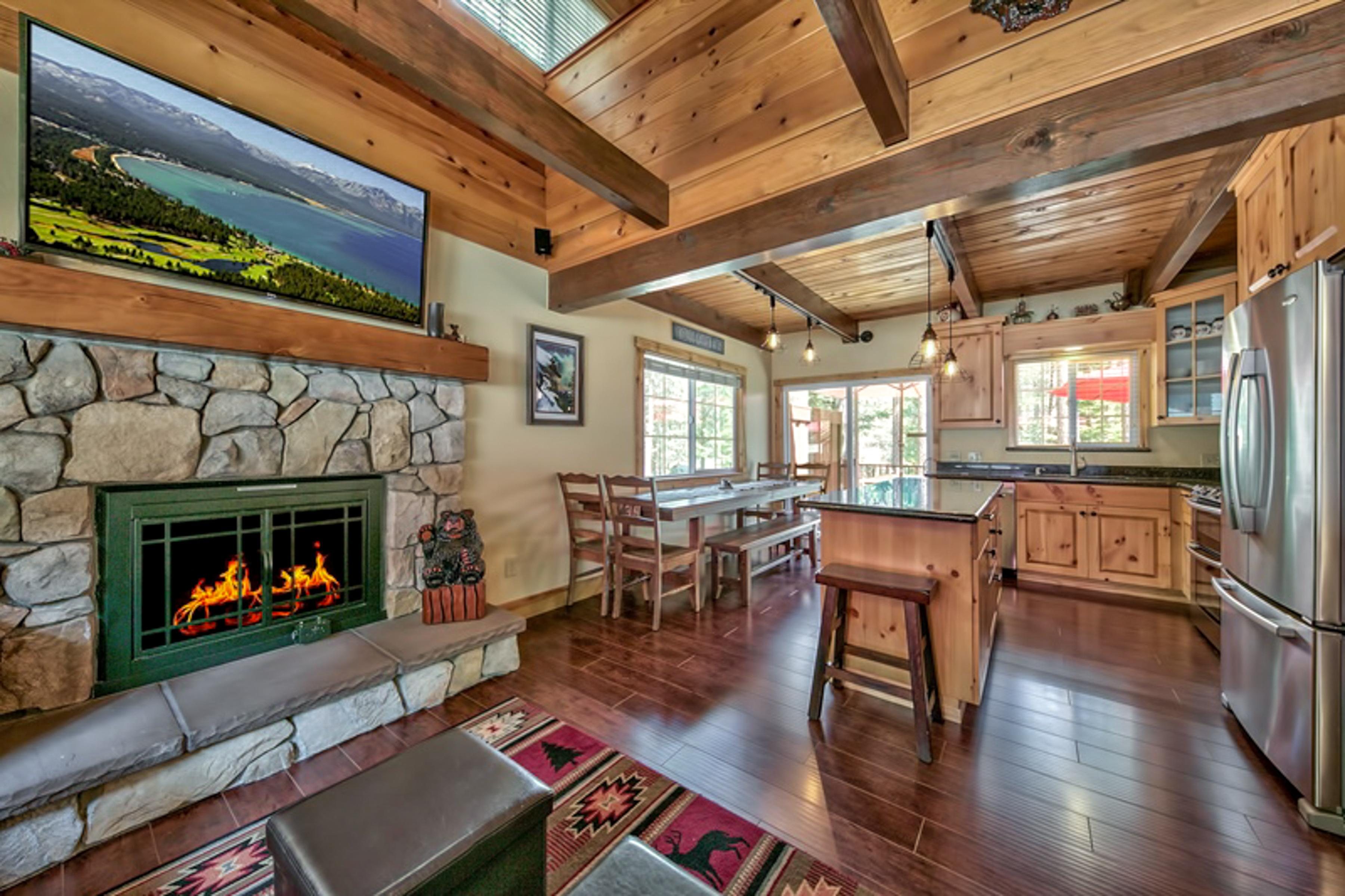 Welcome to South Lake Tahoe! A large flat screen TV sits over the gas fireplace in the open living room.