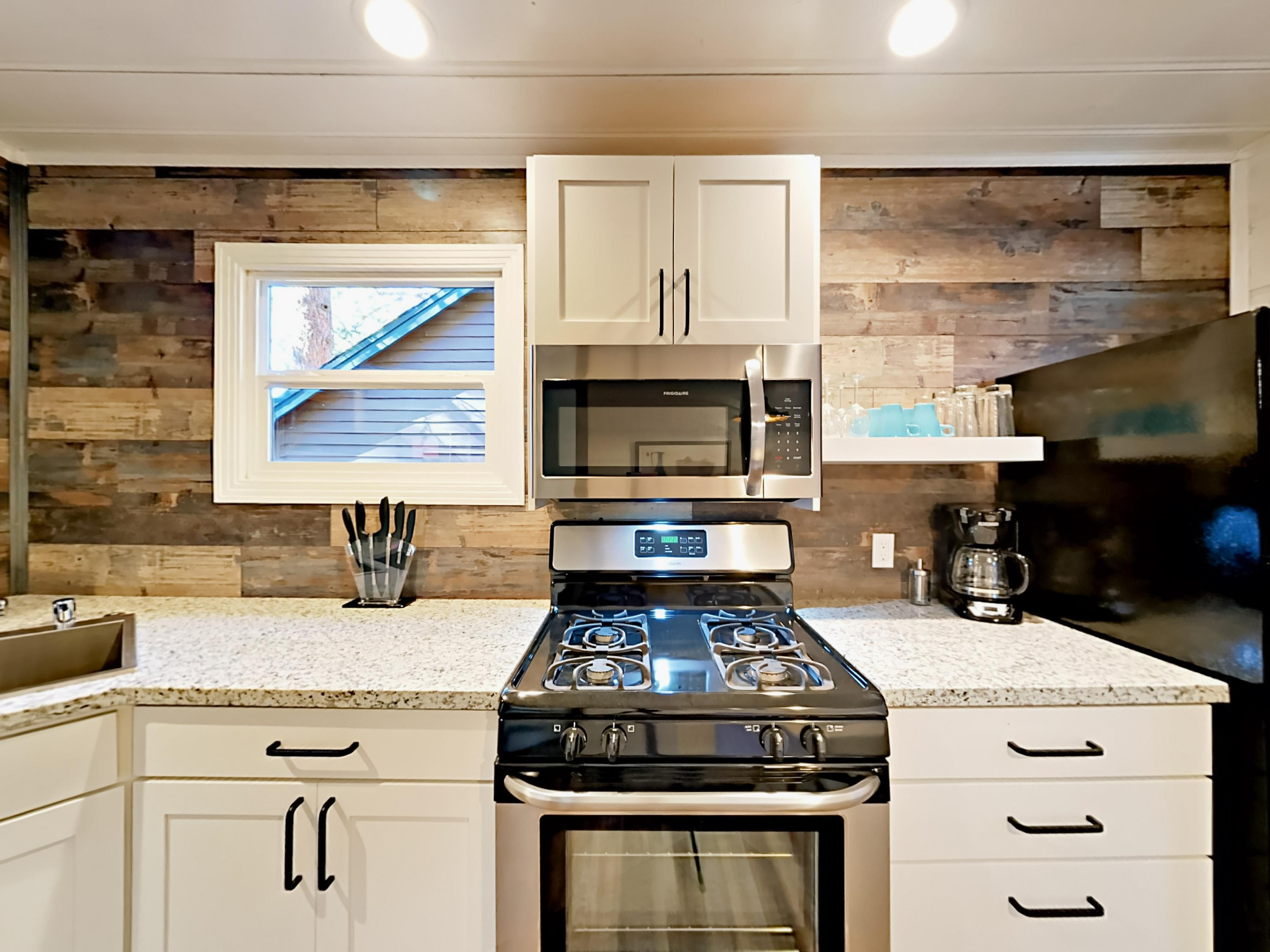 The kitchen is outfitted with a full suite of stainless steel appliances, including a gas range.