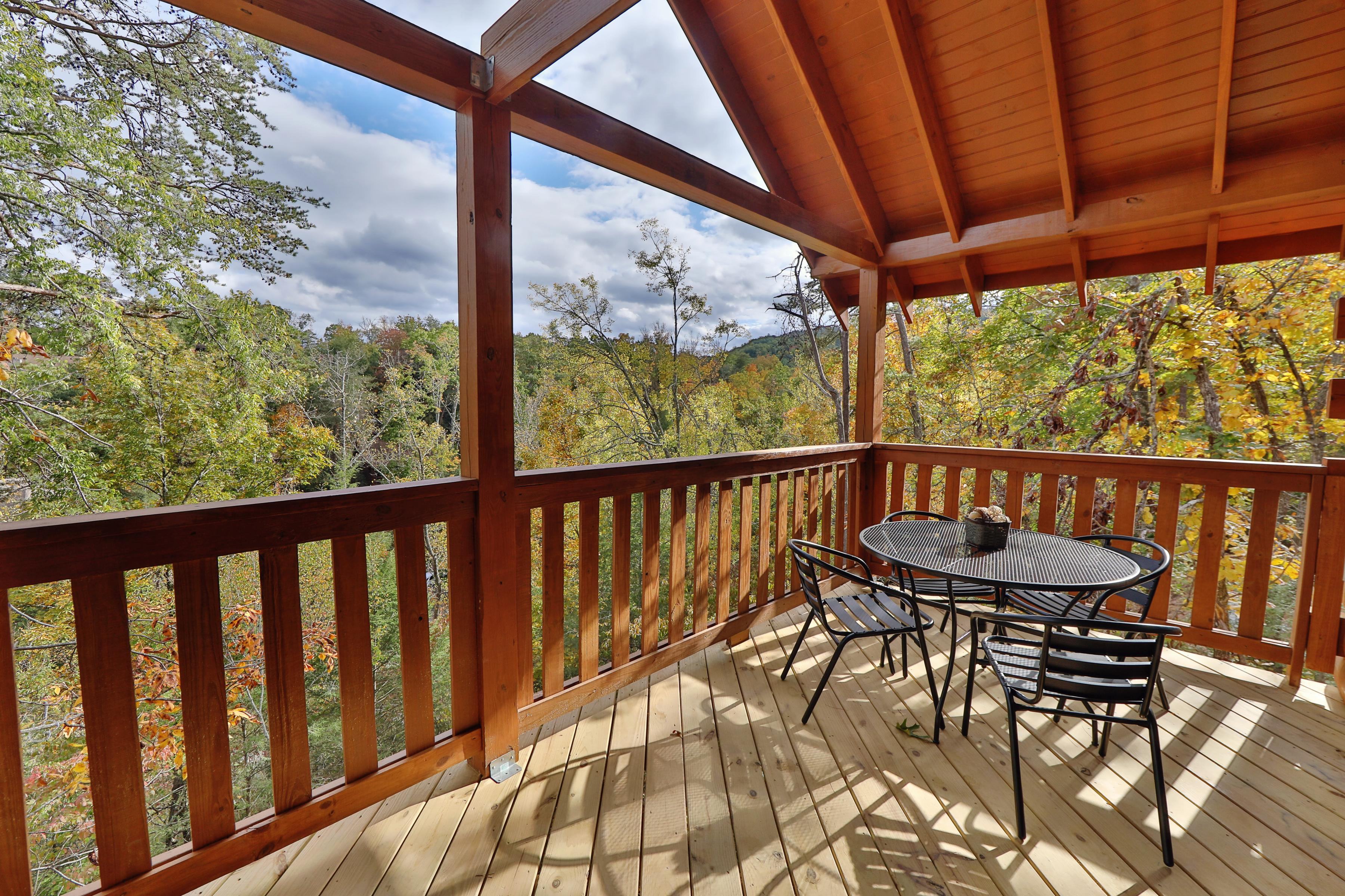Seating for 4 and a gas grill await on an upper deck, set among the treetops.
