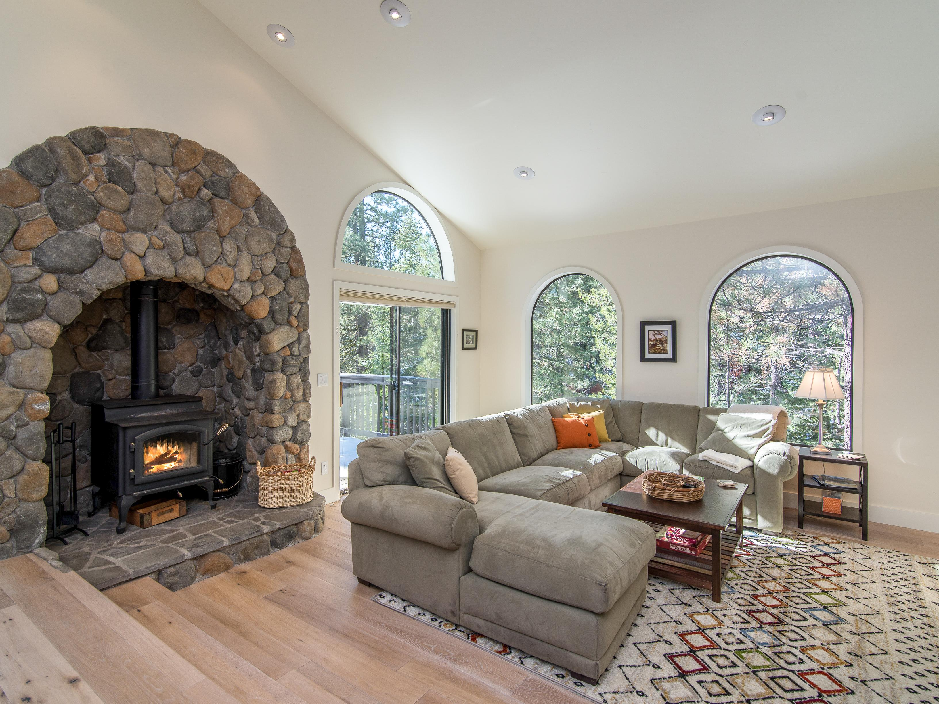 Welcome to Truckee! Your rental is professionally managed by TurnKey Vacation Rentals.Inviting living room with wood burning stove and cozy sectional couch.