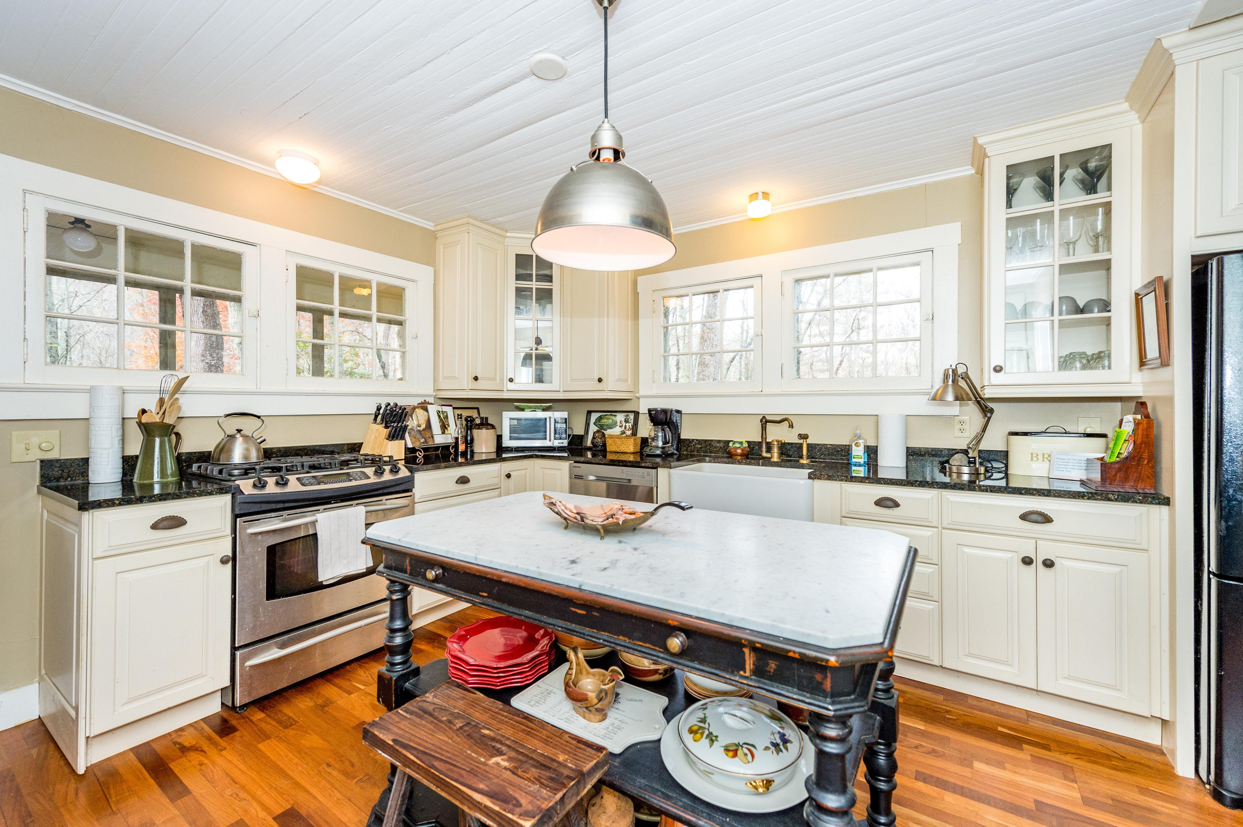 Country kitchen with gas range, farm-style sink, and marble island.
